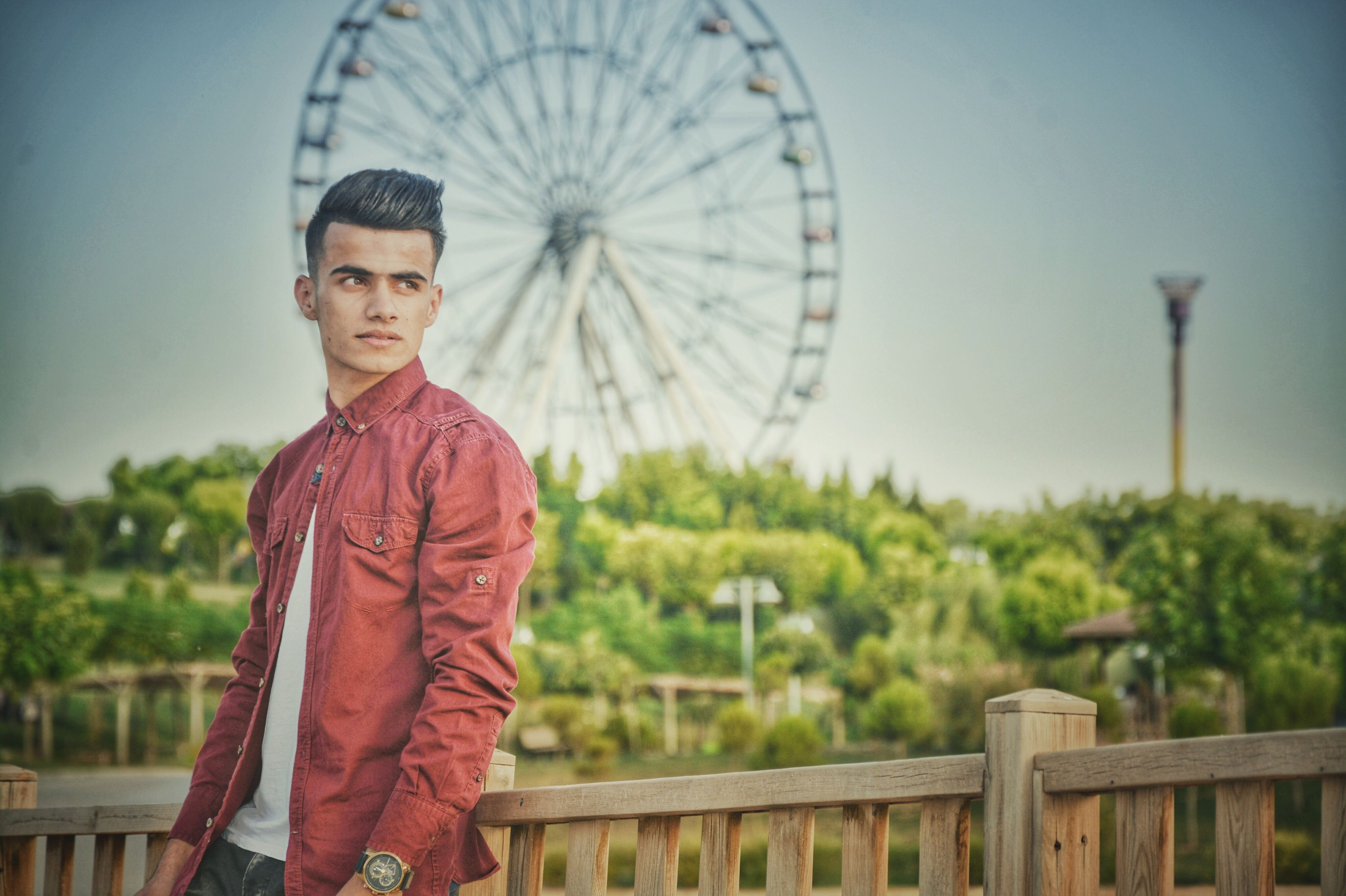 real people, casual clothing, looking at camera, focus on foreground, leisure activity, day, standing, front view, portrait, outdoors, lifestyles, one person, ferris wheel, young men, young adult, clear sky, sky, architecture, tree