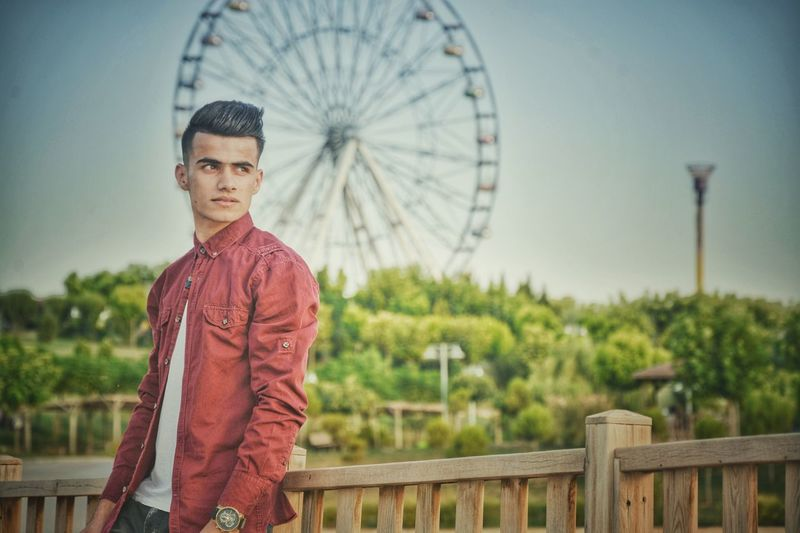 People Lifestyles Real People Day Casual Clothing Ferris Wheel Leisure Activity Outdoors Looking At Camera Portrait Standing One Person Clear Sky Young Adult Sky Adult
