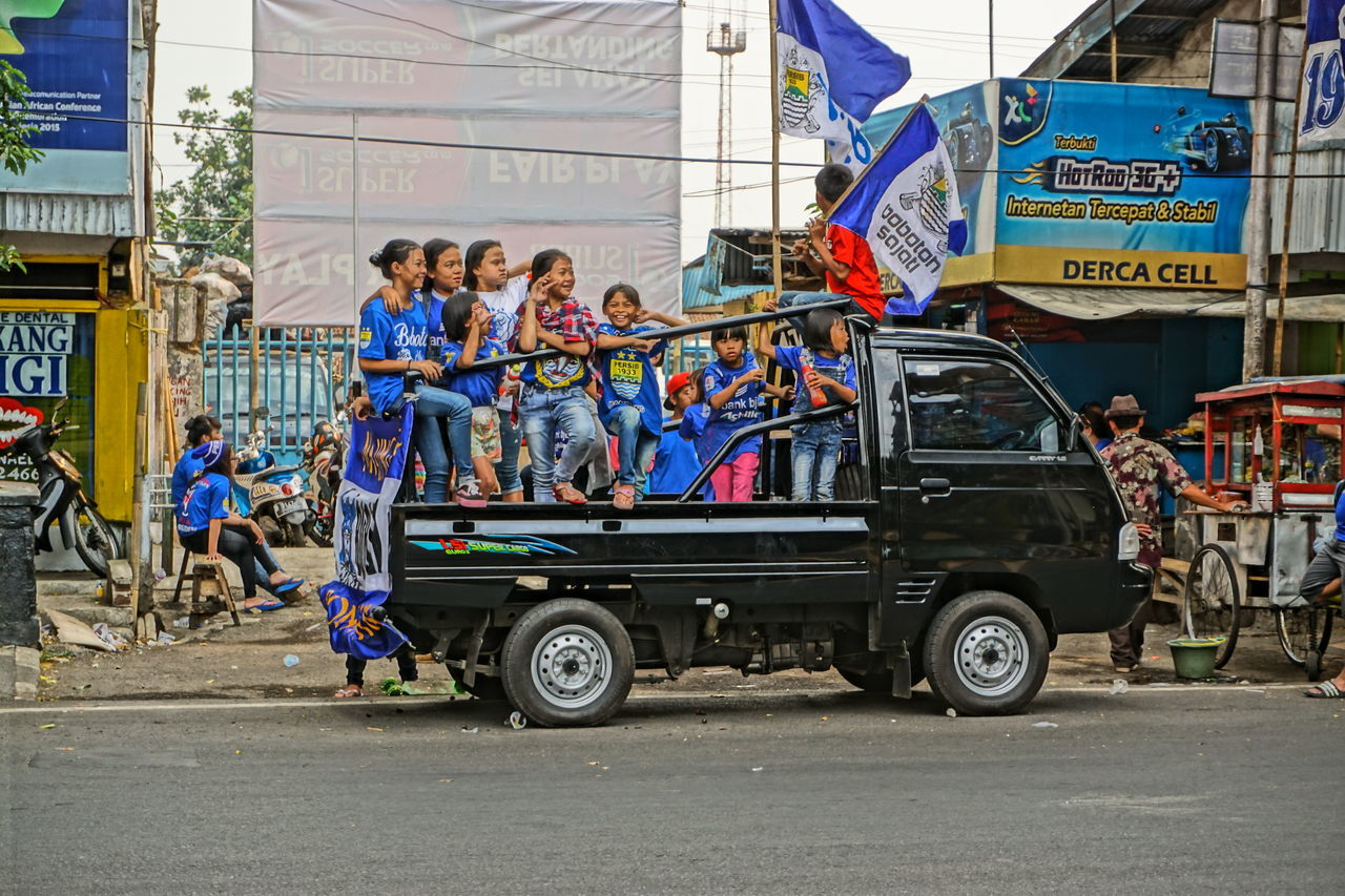 day, transportation, street, outdoors, car, real people, men, women, flag, road, togetherness, building exterior, built structure, full length, city, architecture, adult, people, adults only