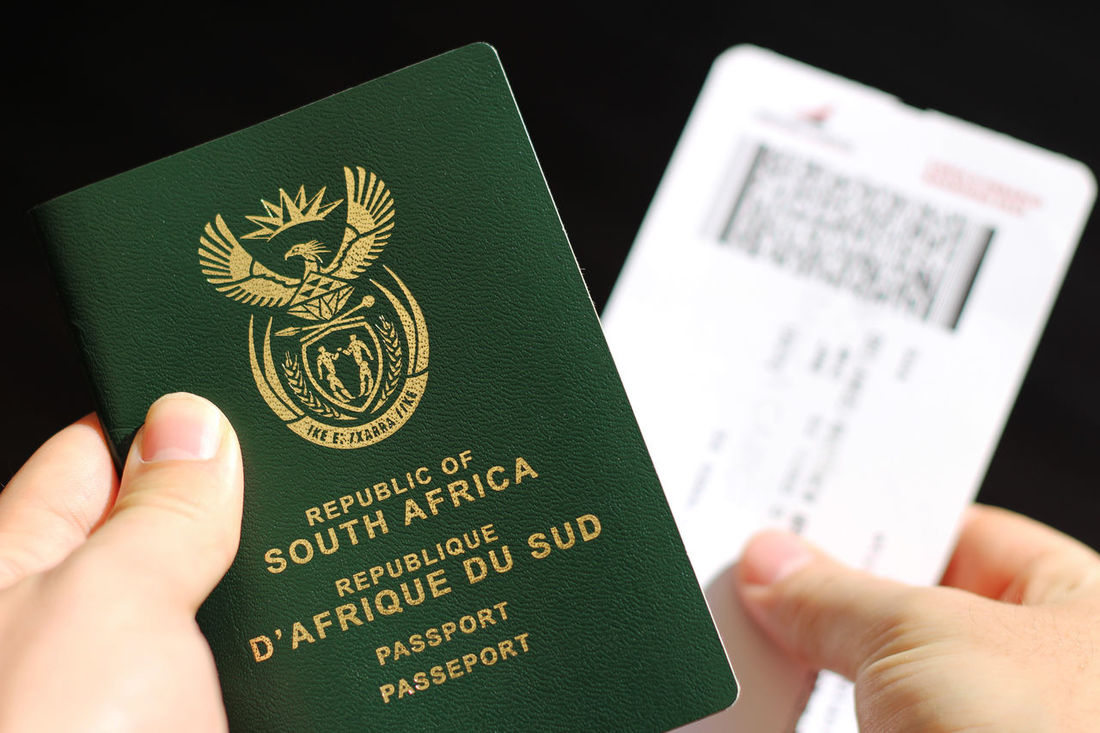 A man holding a passport and a plane ticket Green Color NOMAD Places To See Before You Die South Africa Travel Traveling Wunderlust Black Background Close-up Day Exploration Hard Light Holding Human Body Part Human Hand One Person Passport Pattern Places To See Plane Ticket Real People Tourism Travel Destinations Travel Documents