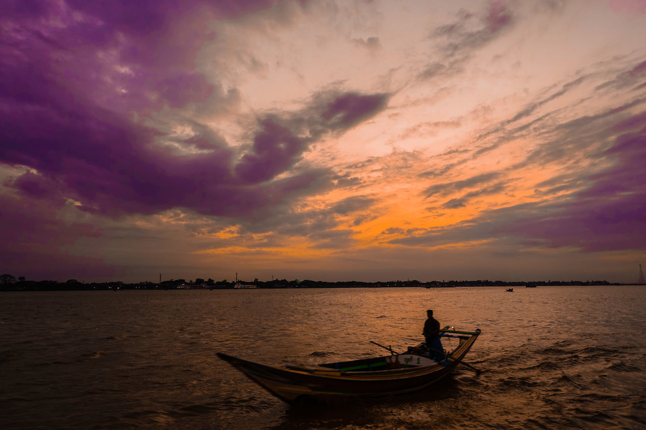 Silhouette Man On Boat In River Against Cloudy Sky During Sunset