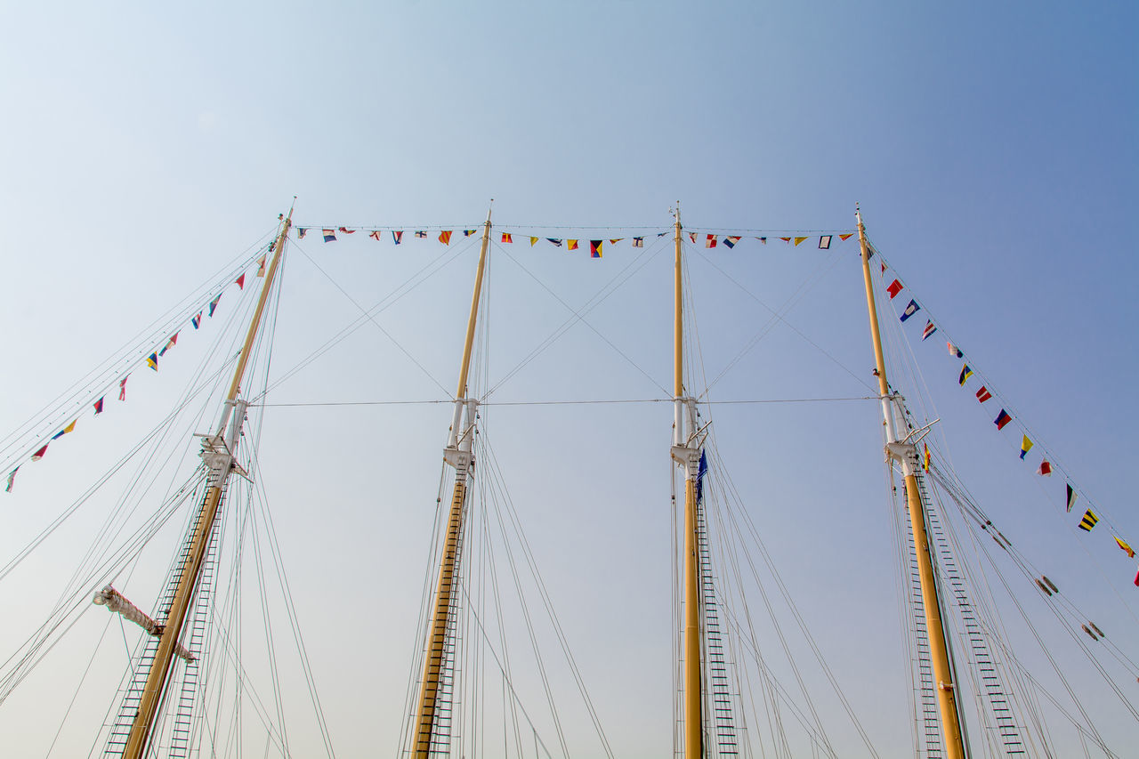 Flags Hanging On Masts Against Cleat Sky