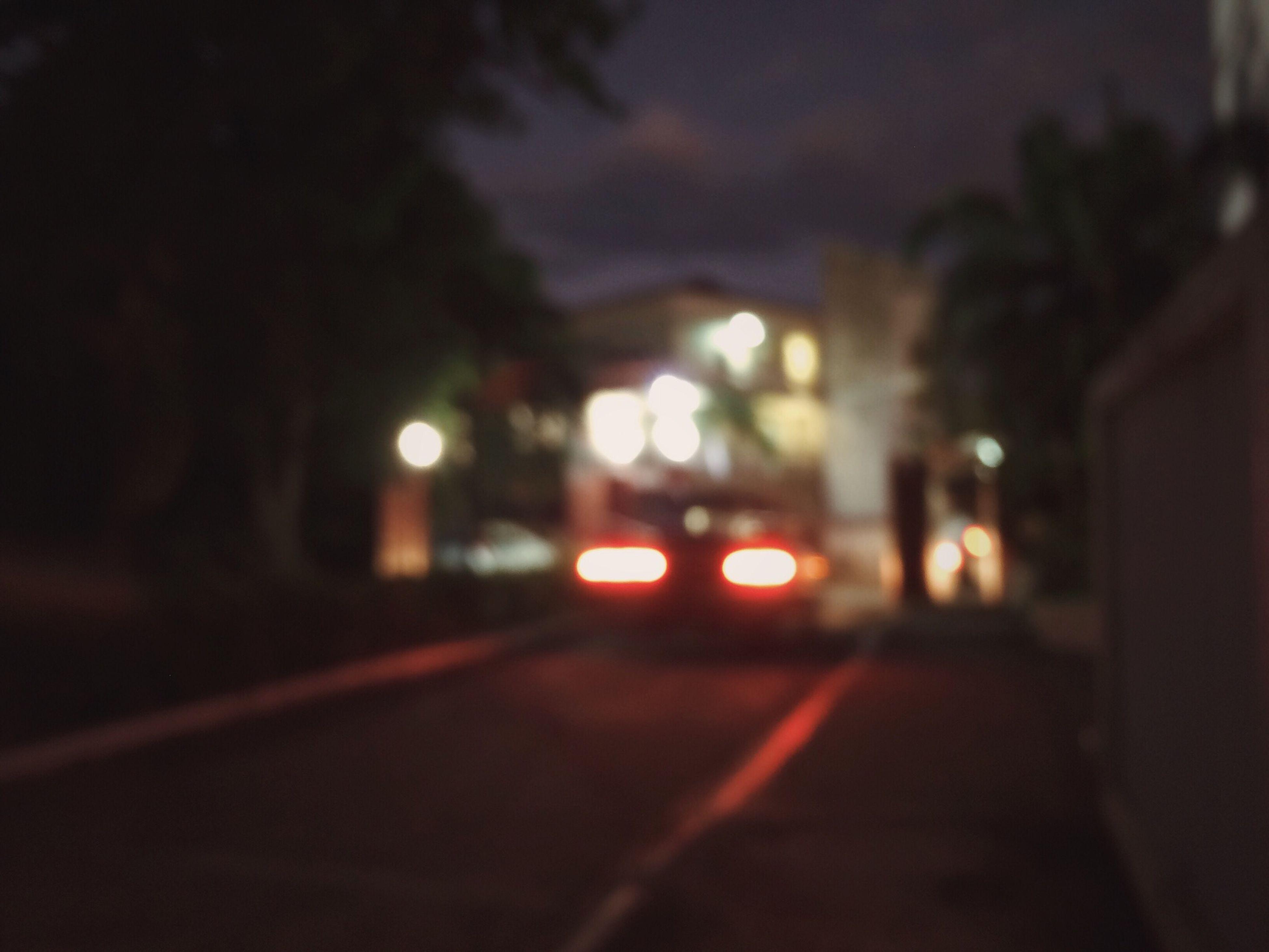 illuminated, night, transportation, street, the way forward, road, defocused, car, street light, land vehicle, city, building exterior, lighting equipment, dark, mode of transport, architecture, built structure, surface level, road marking, city street