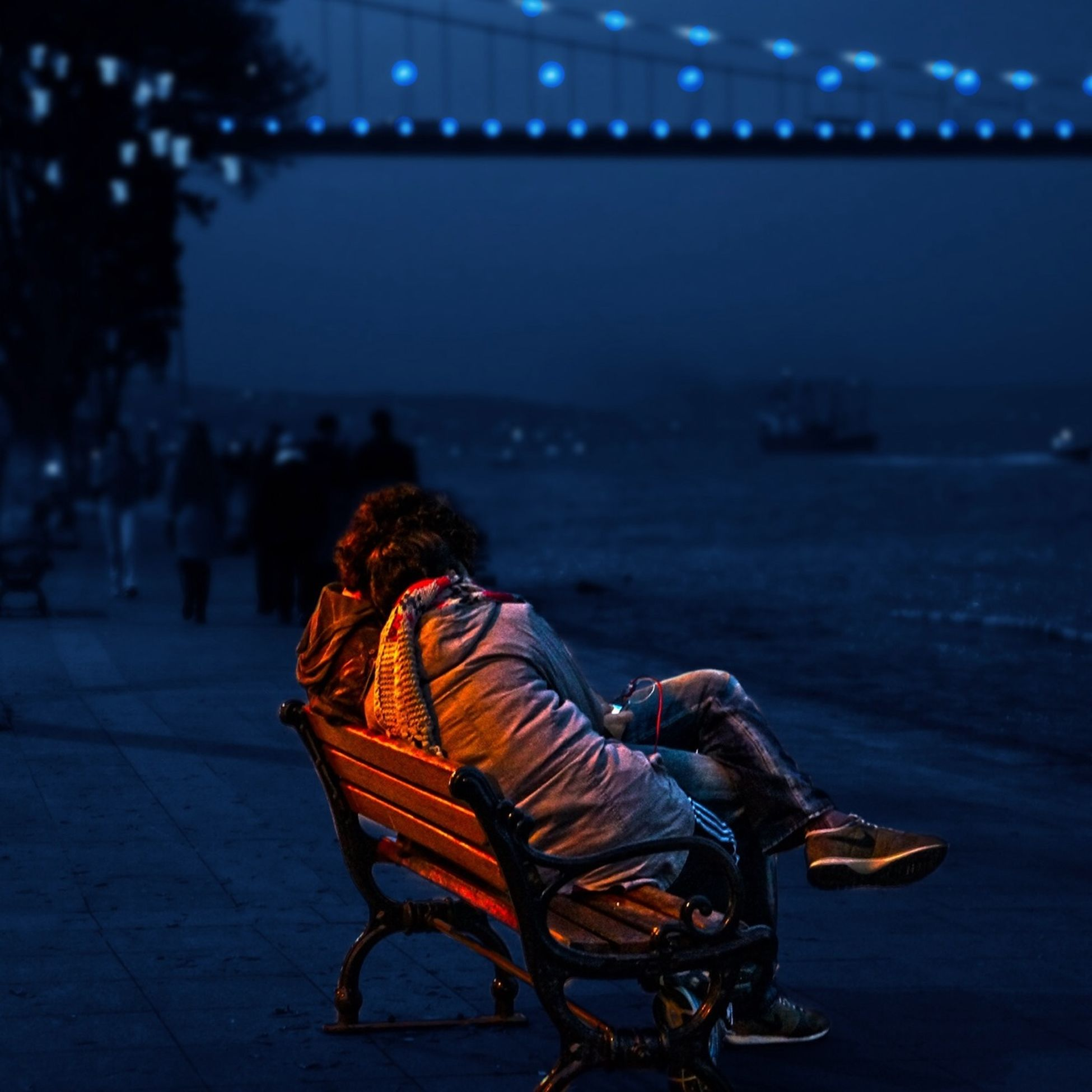 lifestyles, leisure activity, men, sitting, person, night, rear view, illuminated, relaxation, focus on foreground, casual clothing, water, outdoors, full length, sea, togetherness, arts culture and entertainment