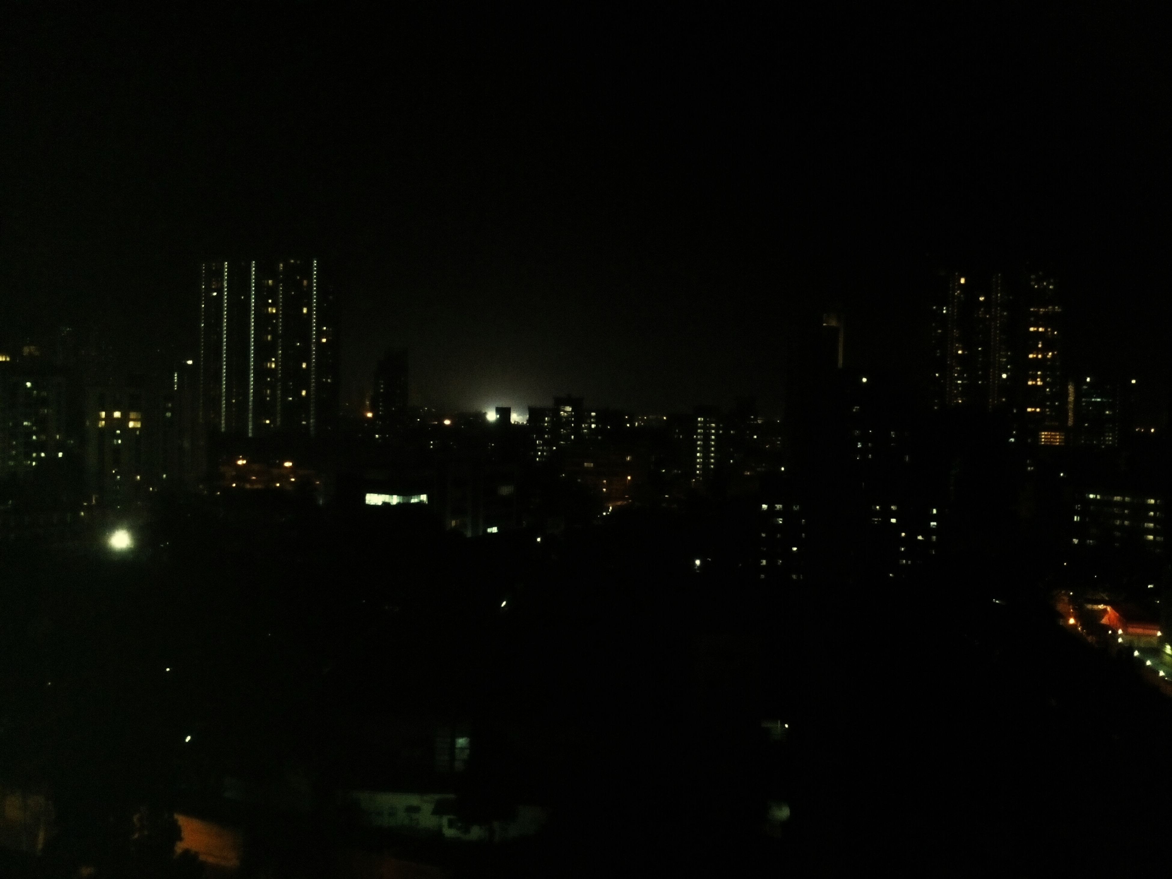night, illuminated, city, building exterior, architecture, cityscape, built structure, skyscraper, urban skyline, modern, office building, tower, tall - high, dark, copy space, city life, crowded, clear sky, development, high angle view