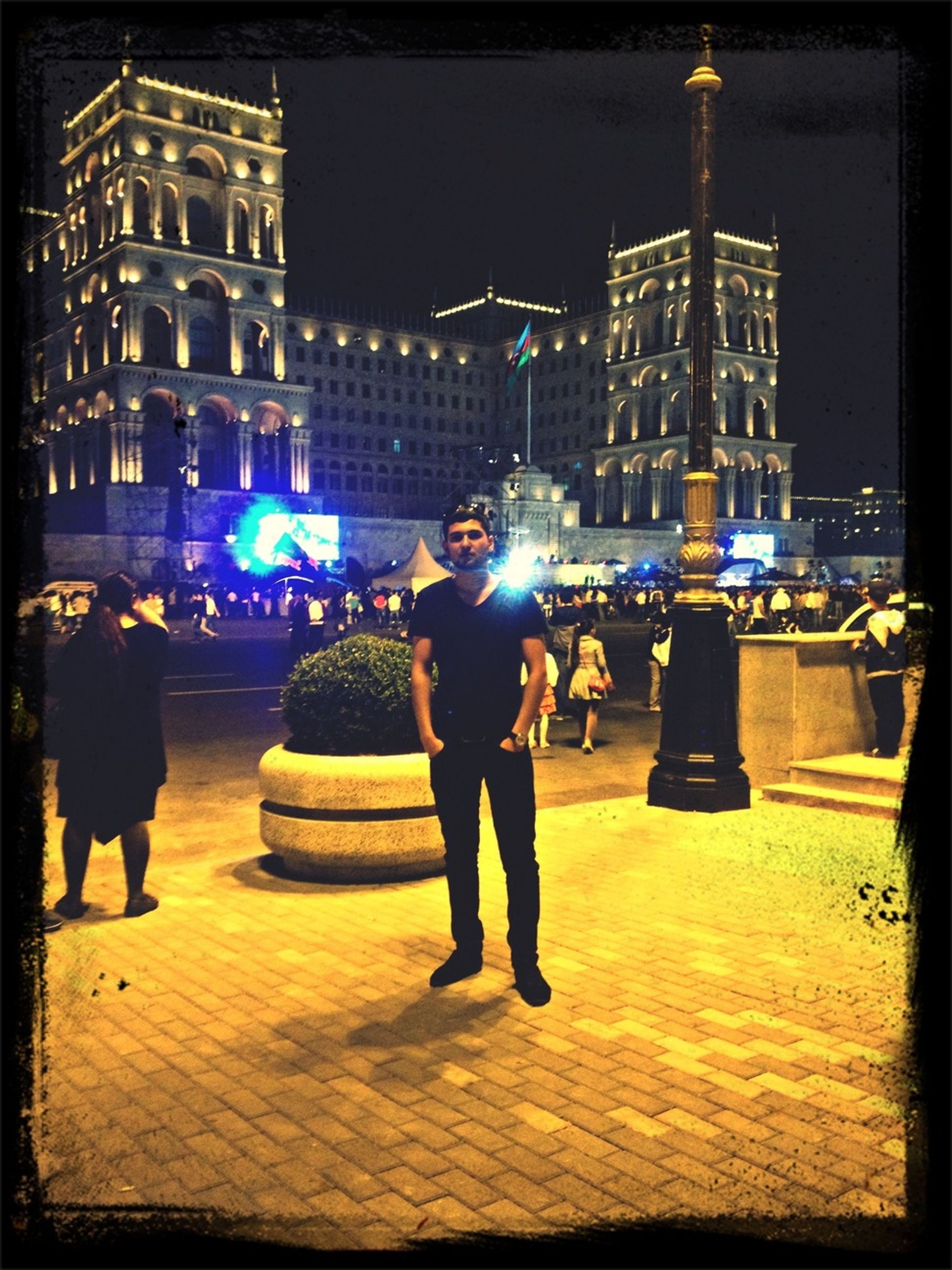 illuminated, building exterior, night, lifestyles, architecture, built structure, leisure activity, city, men, transfer print, city life, full length, casual clothing, person, street, auto post production filter, standing, walking, rear view