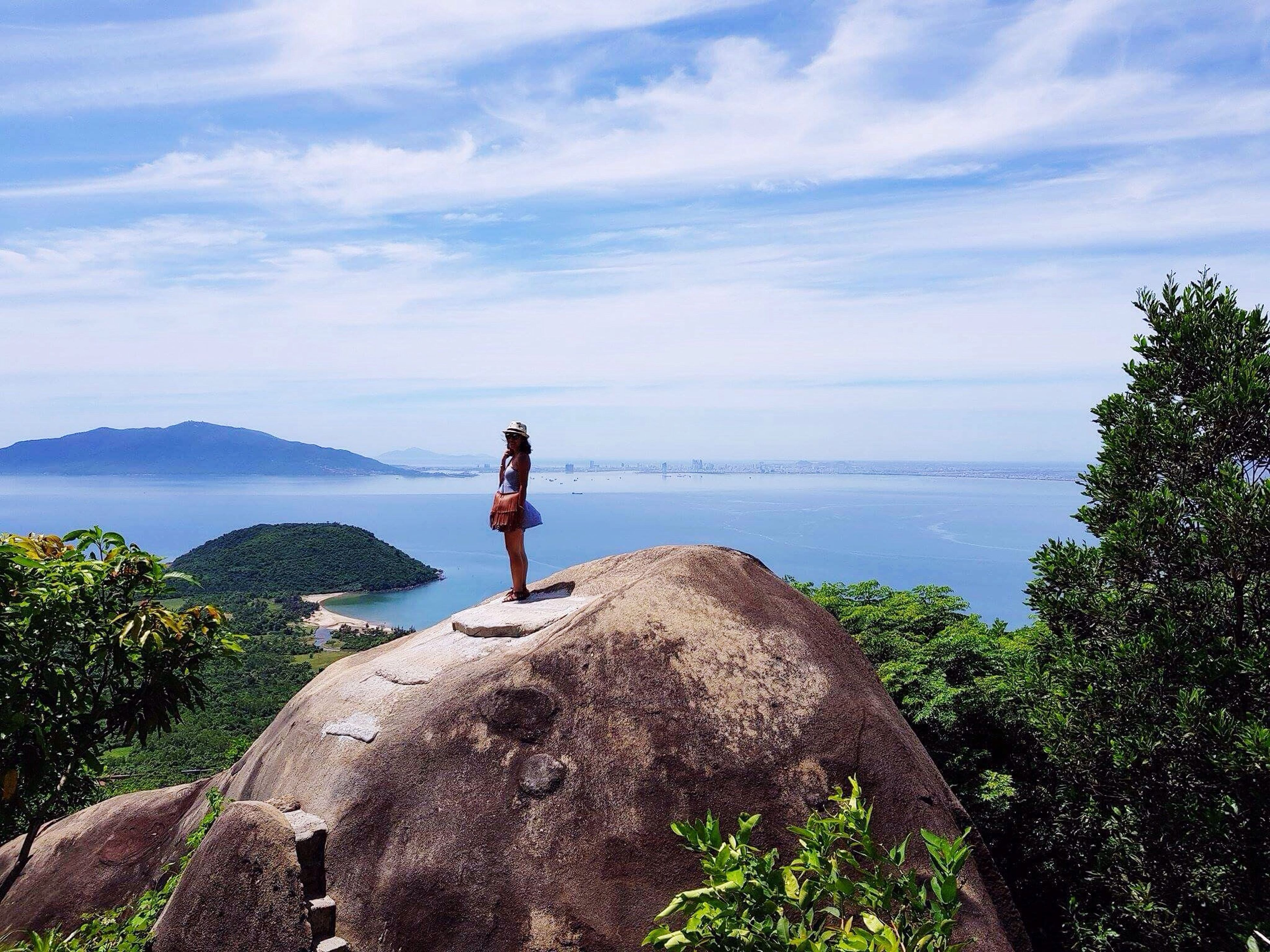 full length, one person, real people, rock - object, sky, nature, scenics, leisure activity, beauty in nature, water, day, sea, standing, cloud - sky, tranquility, rear view, tranquil scene, outdoors, lifestyles, tree, horizon over water, mountain, cliff, adventure, men, young women, young adult, people