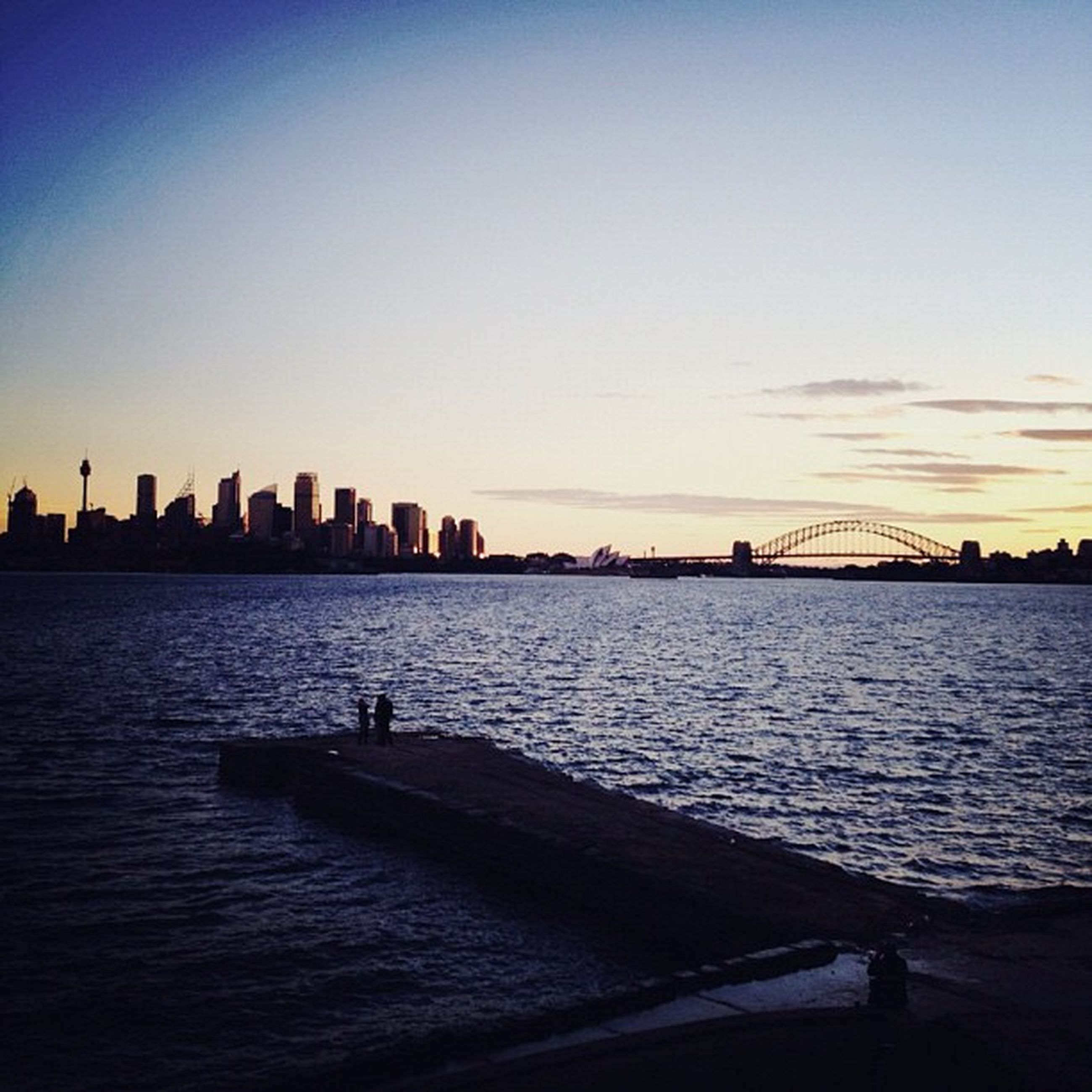water, architecture, built structure, building exterior, city, sunset, cityscape, river, sea, waterfront, urban skyline, skyscraper, silhouette, copy space, sky, skyline, clear sky, rippled, mid distance, scenics