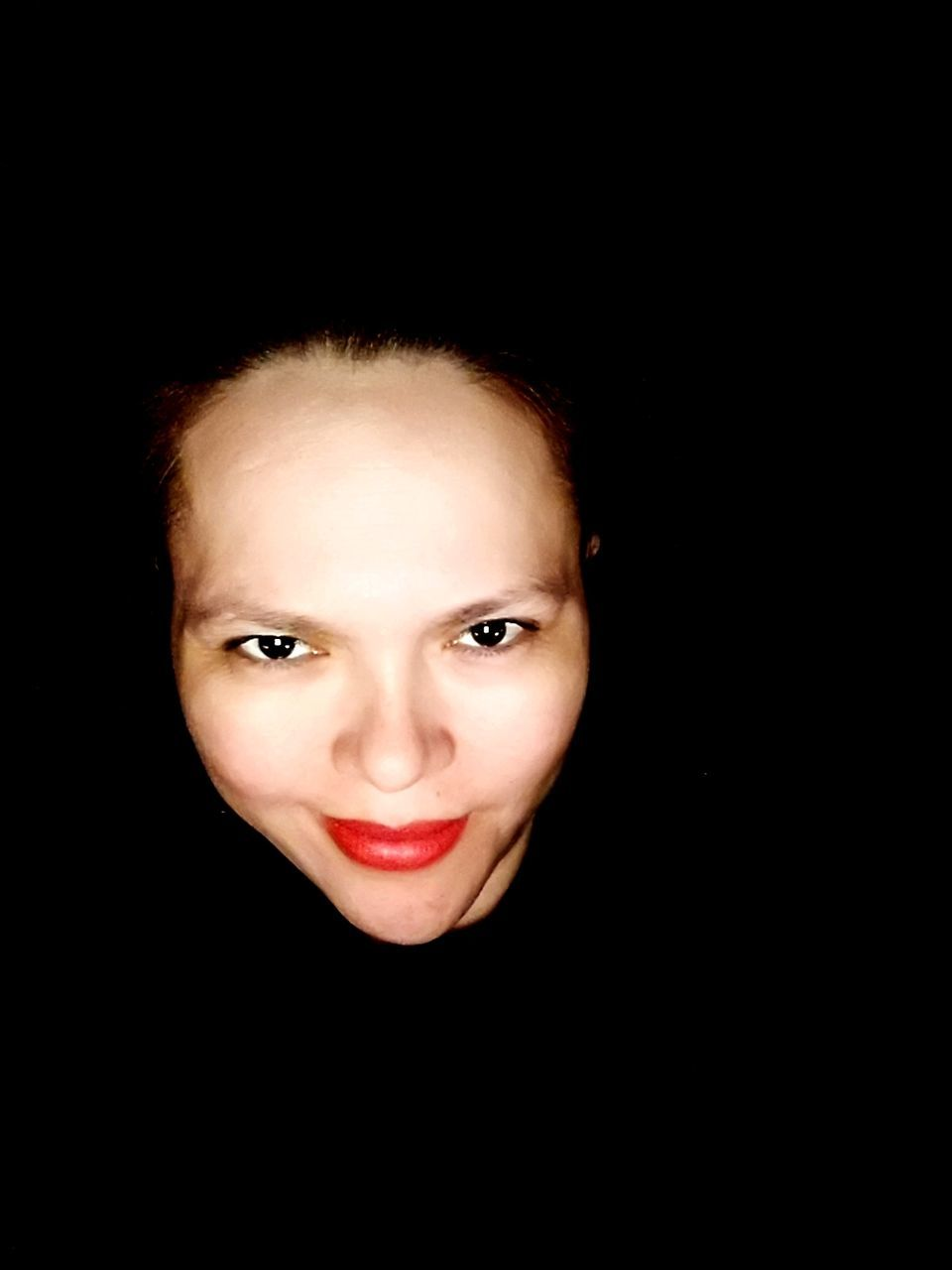 Close-Up Portrait Of Woman Smiling Against Black Background