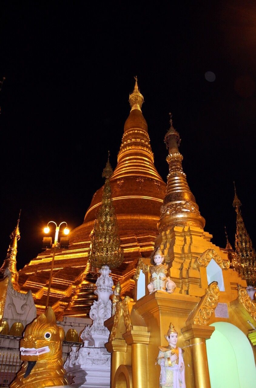 religion, place of worship, spirituality, pagoda, statue, gold colored, architecture, travel destinations, sky, low angle view, building exterior, night, sculpture, outdoors, built structure, no people, illuminated