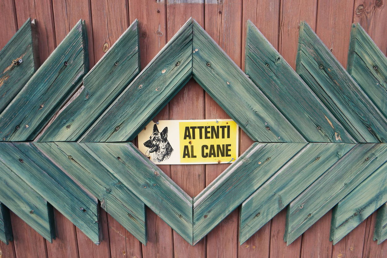 beware of the dog Attenti Al Cane Beware Of The Dog Communication Damaged Door Exterior Geometry Horizontal Symmetry Information No People Sign Symmetry Text Wood Wood - Material Wooden Color Palette