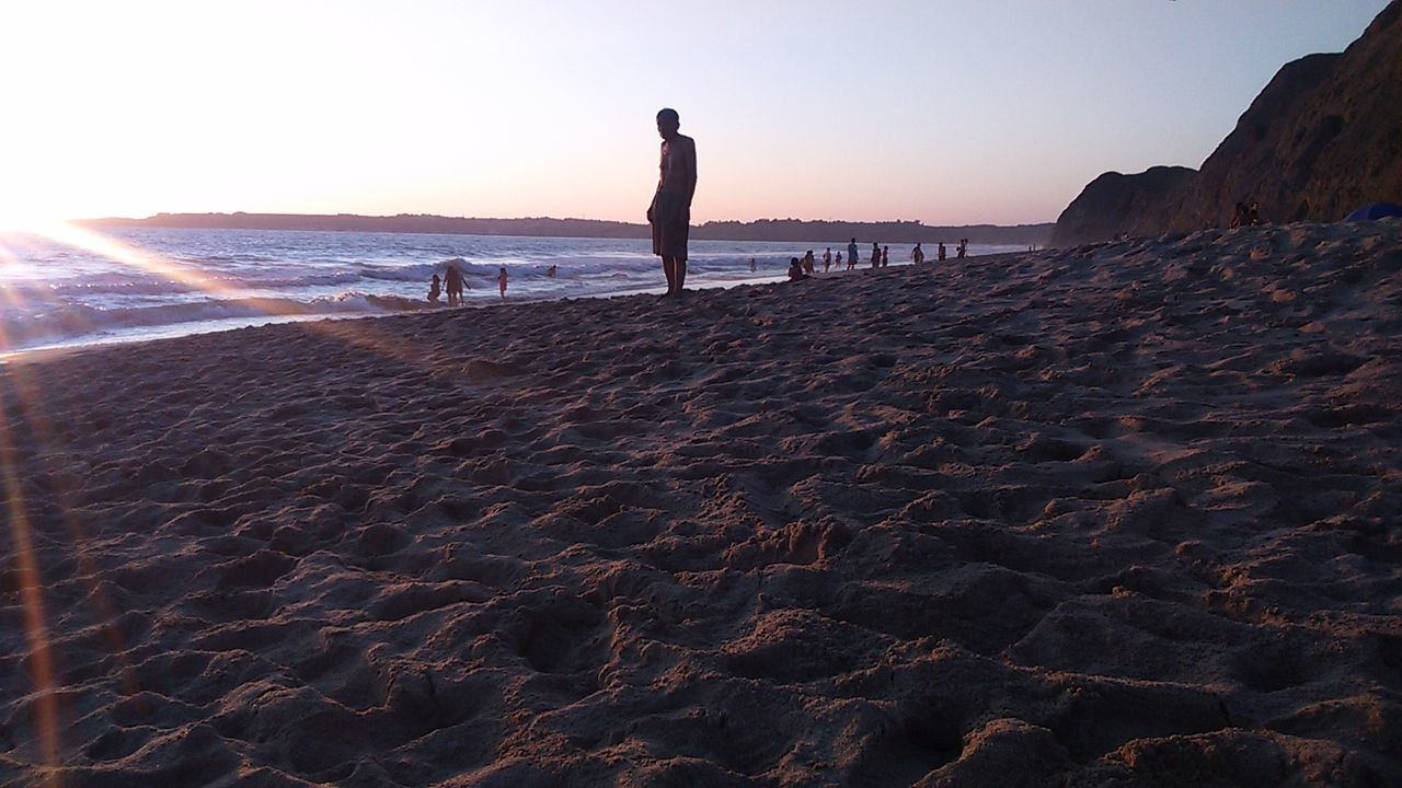 beach, sea, sand, shore, sunset, real people, nature, one person, scenics, leisure activity, water, horizon over water, silhouette, standing, beauty in nature, sky, clear sky, full length, lifestyles, vacations, outdoors, wave, men, day, people