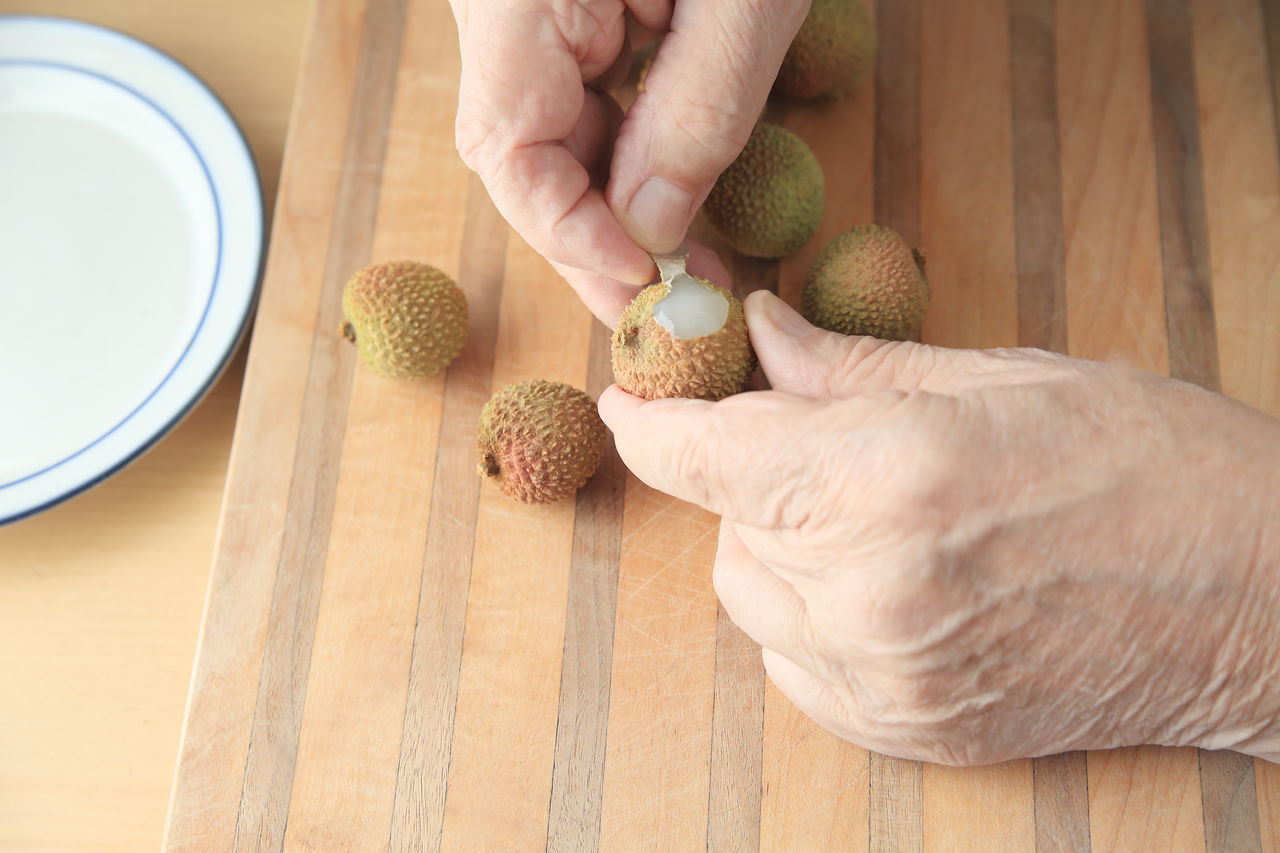 Peeling a fresh lychee fruit Asian Fruit Close-up Copy Space Cutting Board Dish Fingers Food Preparation Hands Healthy Eating Holding Indoors  Juicy Lychees Man Natural Light One Person Overhead Peeling Ripe Tasty Textures Wood Surface