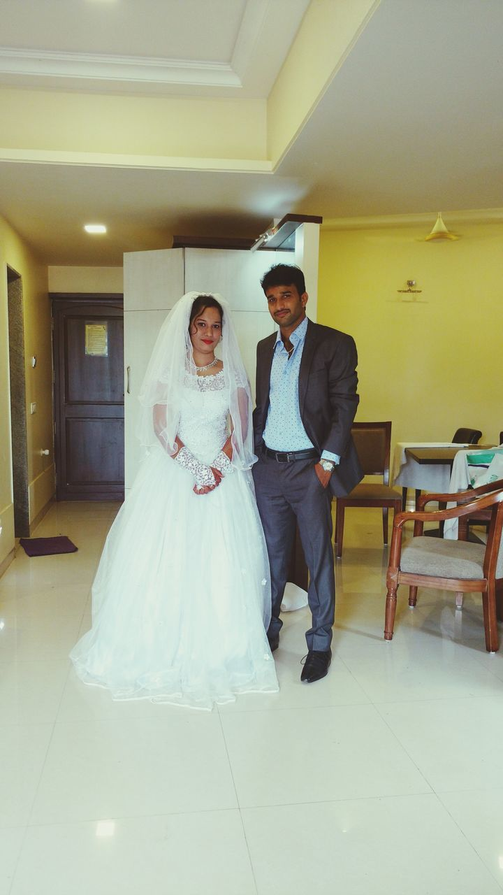 wedding, bride, indoors, full length, wedding dress, real people, young women, life events, men, love, bridegroom, women, well-dressed, happiness, young adult, standing, togetherness, suit, groom, architecture, day, people