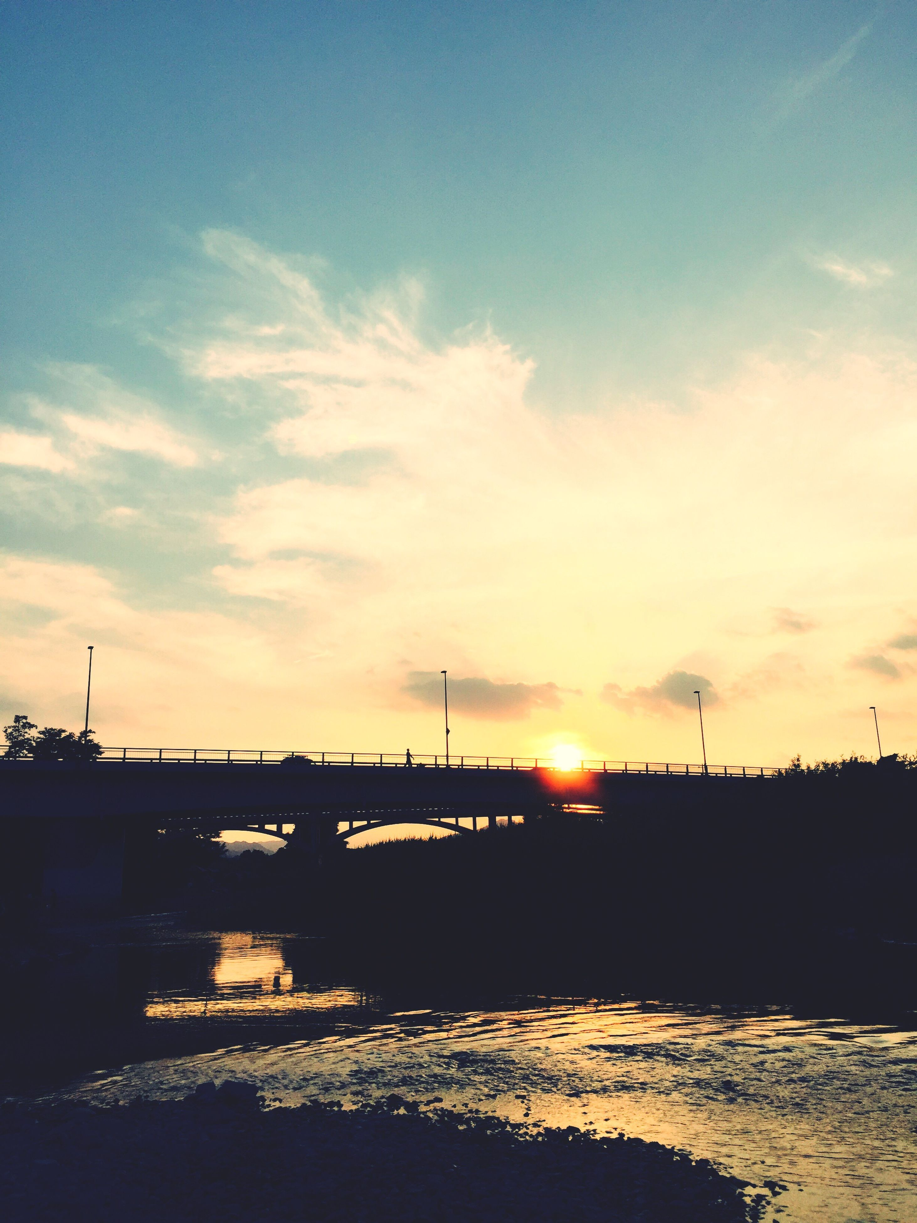 water, river, bridge - man made structure, sunset, connection, waterfront, architecture, built structure, calm, sky, cloud, scenics, bridge, tranquil scene, engineering, orange color, nature, beauty in nature, outdoors, tranquility, ocean, outline, no people, riverbank