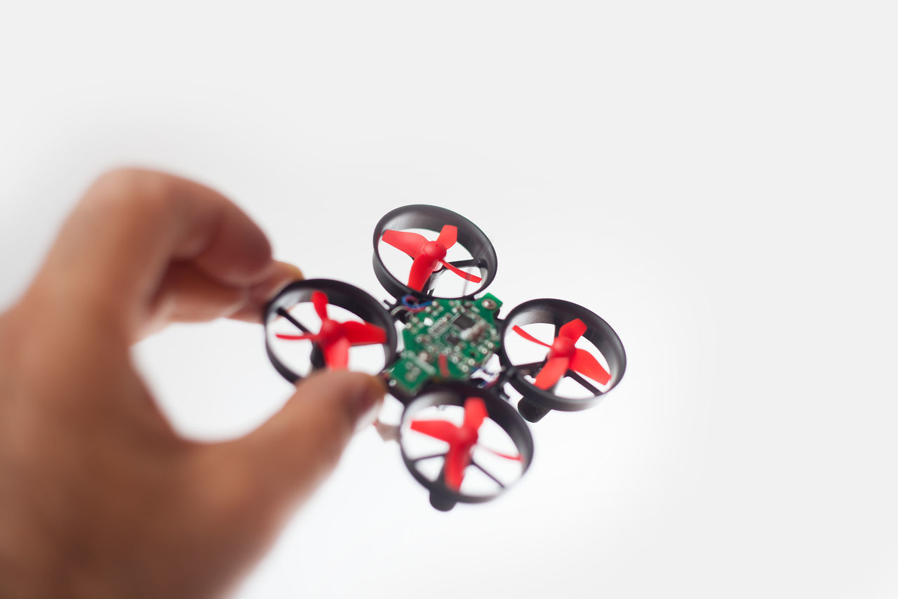 Close-Up Of Hand Holding Drone Over White Background