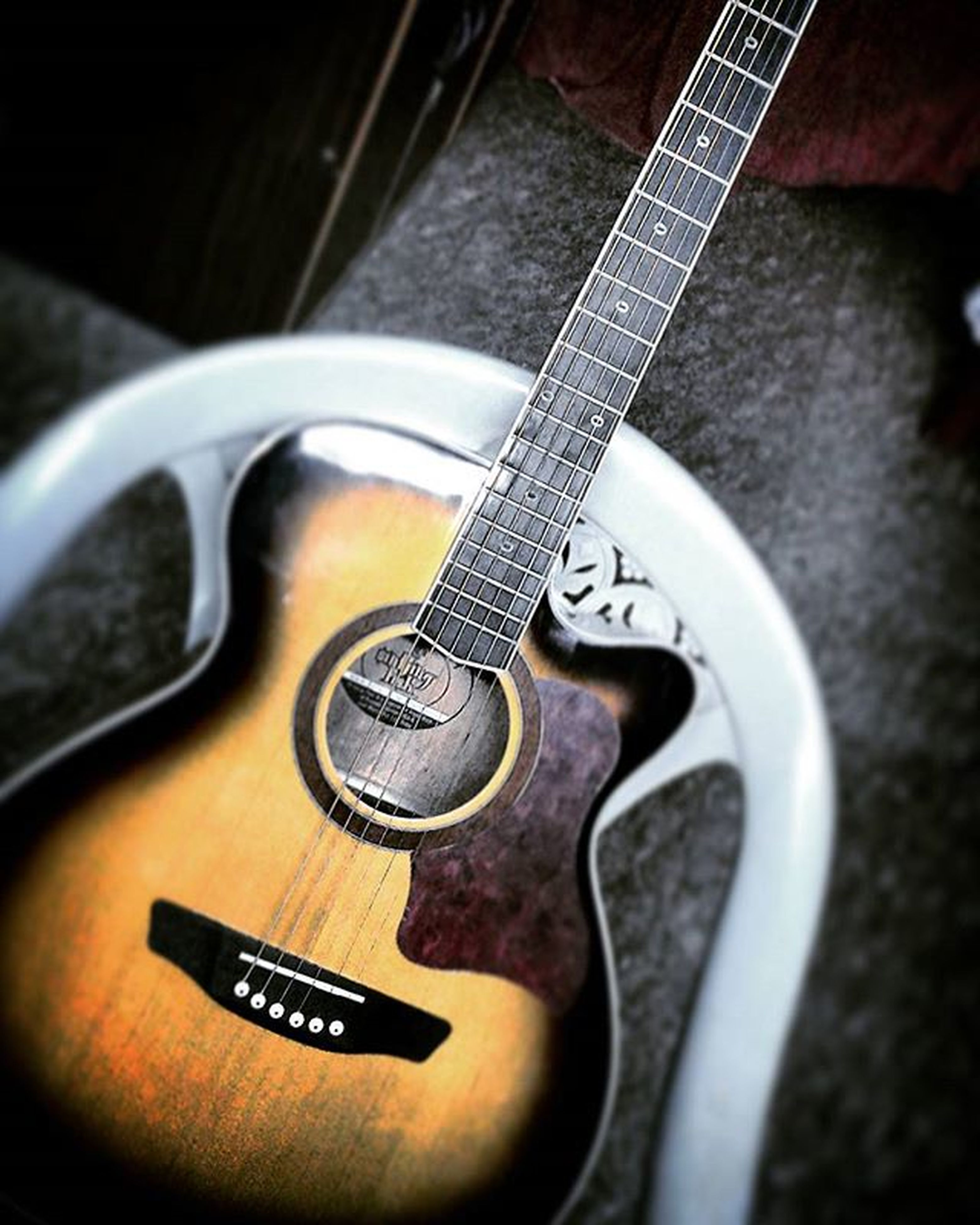 music, musical instrument, guitar, musical equipment, indoors, close-up, musical instrument string, arts culture and entertainment, metal, high angle view, acoustic guitar, still life, string instrument, technology, single object, selective focus, connection, equipment, focus on foreground, no people