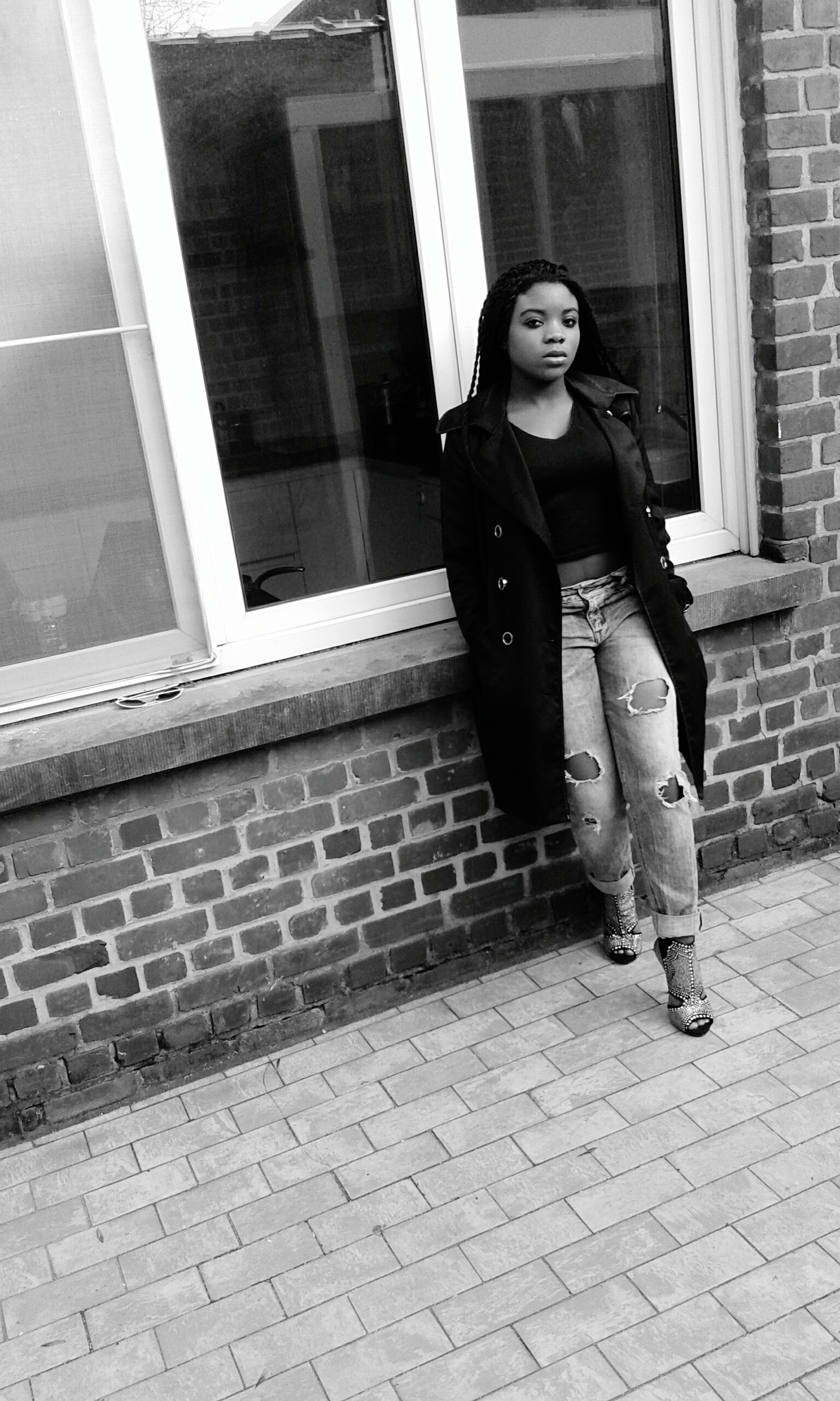 full length, young adult, casual clothing, person, building exterior, lifestyles, architecture, built structure, young women, front view, standing, looking at camera, leisure activity, portrait, steps, brick wall, hands in pockets