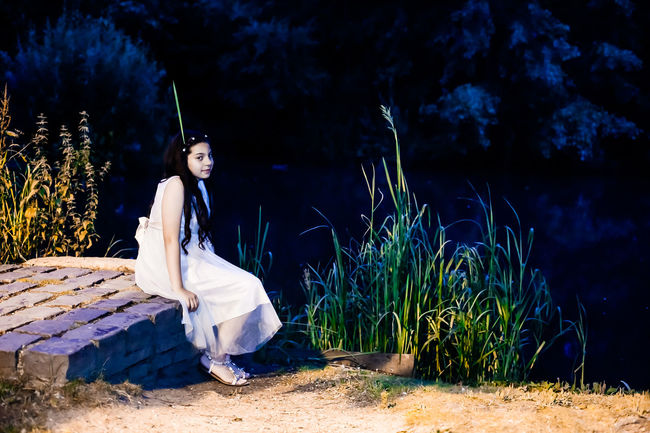 Girl sitting by pond at night in the moonlight Coming Of Age Dark Full Length Girl Happy Junior Prom Magical Moonlight Mysterious Nature Night Nymph Outdoors Plant Pond Pretty Girl Prom Dress Reeds Refelections Relaxation Sandals Sitting White Dress
