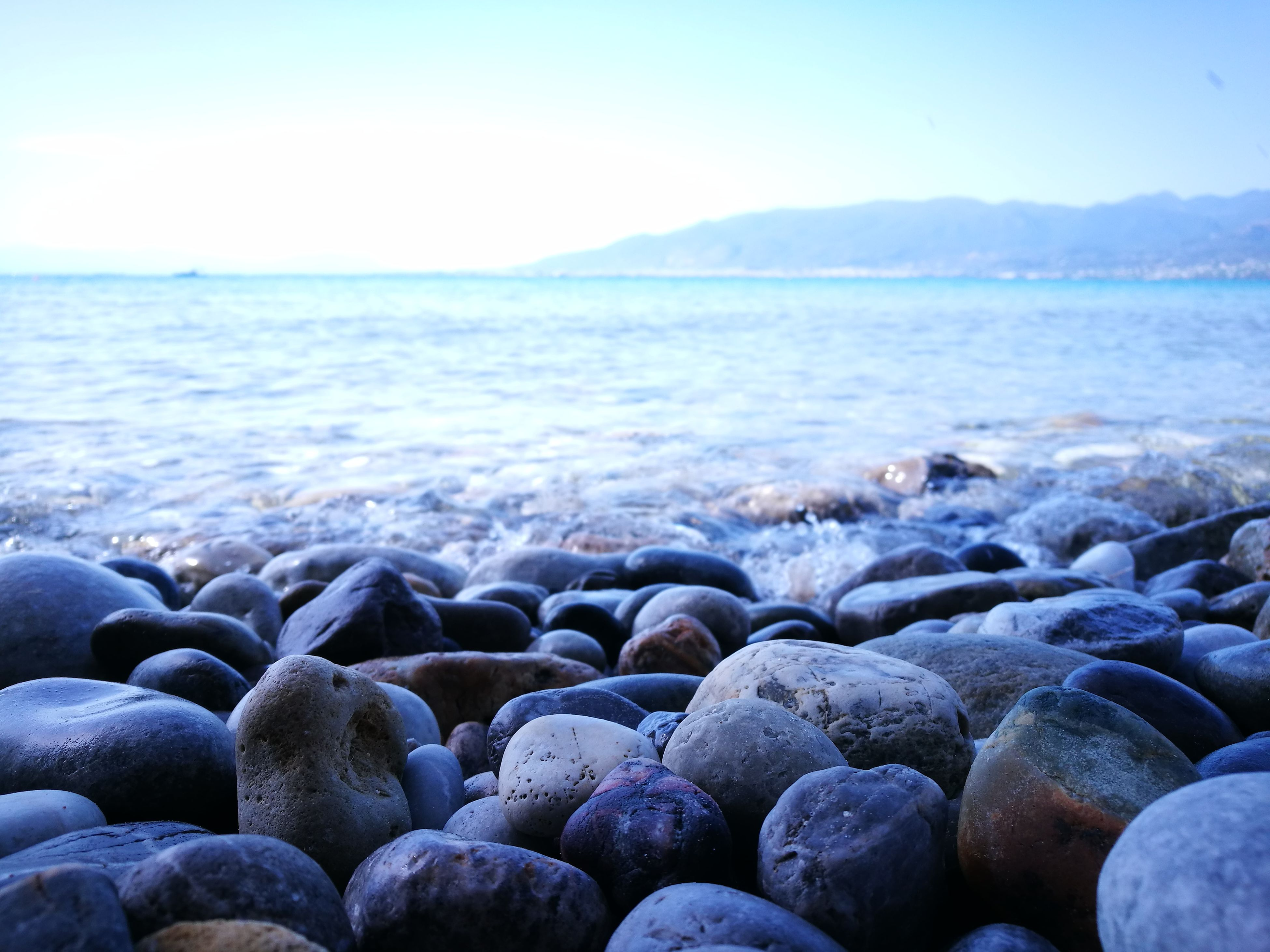 pebble, sea, beach, shore, pebble beach, water, nature, beauty in nature, no people, outdoors, tranquil scene, day, tranquility, scenics, horizon over water, close-up, sky