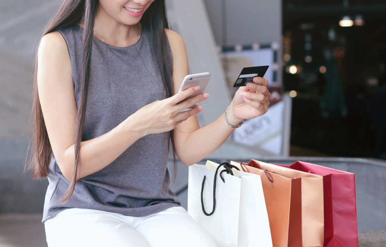 Adult Casual Clothing Cheerful Close-up Communication Connection Credit Card Happiness Holding Indoors  Internet Mobile Phone One Person One Woman Only Online Shopping  Only Women People Portable Information Device Shopping Smart Phone Smiling Technology Wireless Technology Women Young Adult