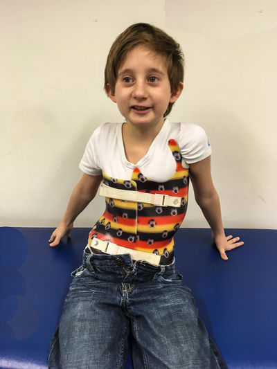 Boy wearing a cheneua back brace sits in a doctors's office Cheneau Brace Childhood Looking At Camera Orthopedics Scoliosis Scoliosis Awareness Month Smiling Three Quarter Length