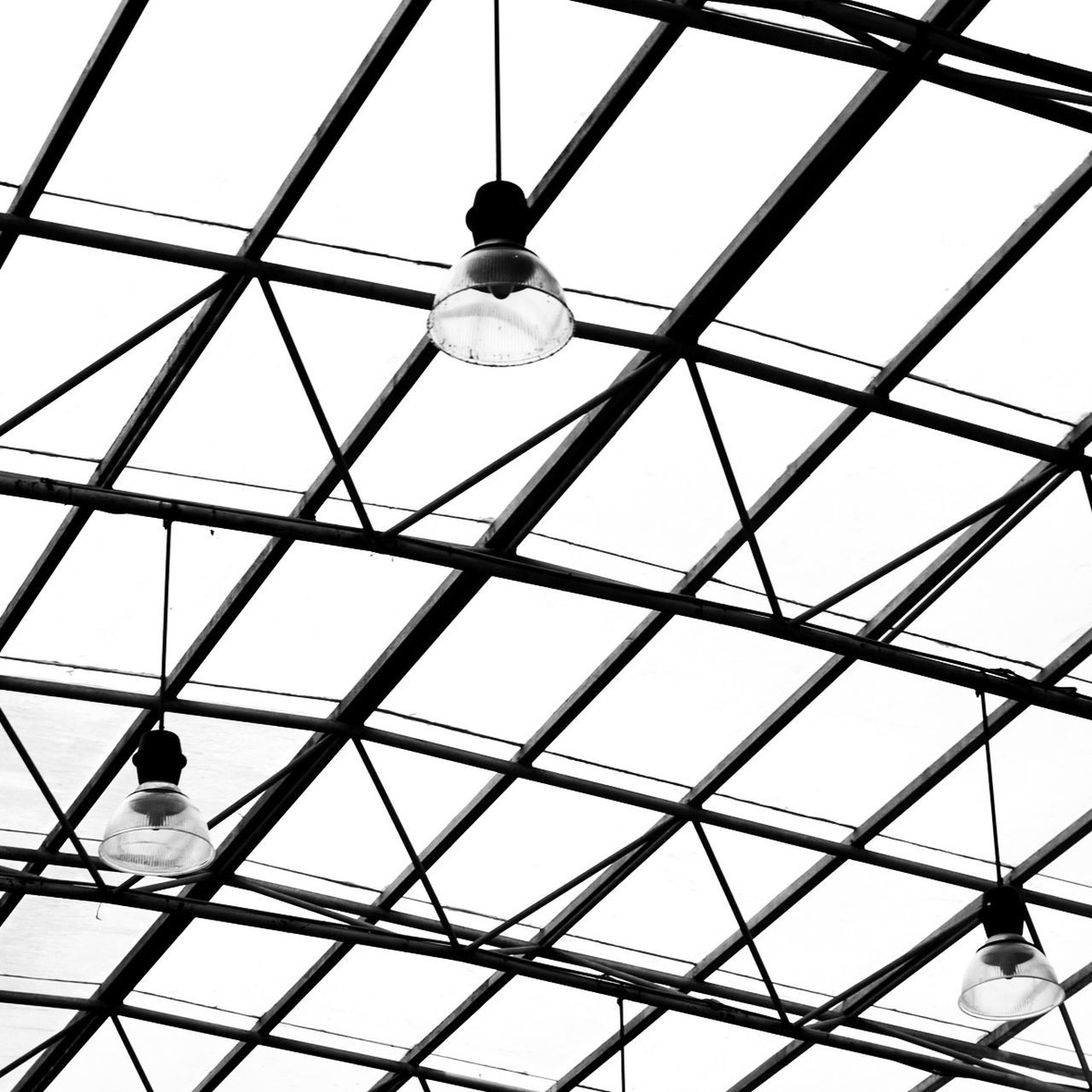 Low Angle View Of Lamps Hanging From Glass Ceiling