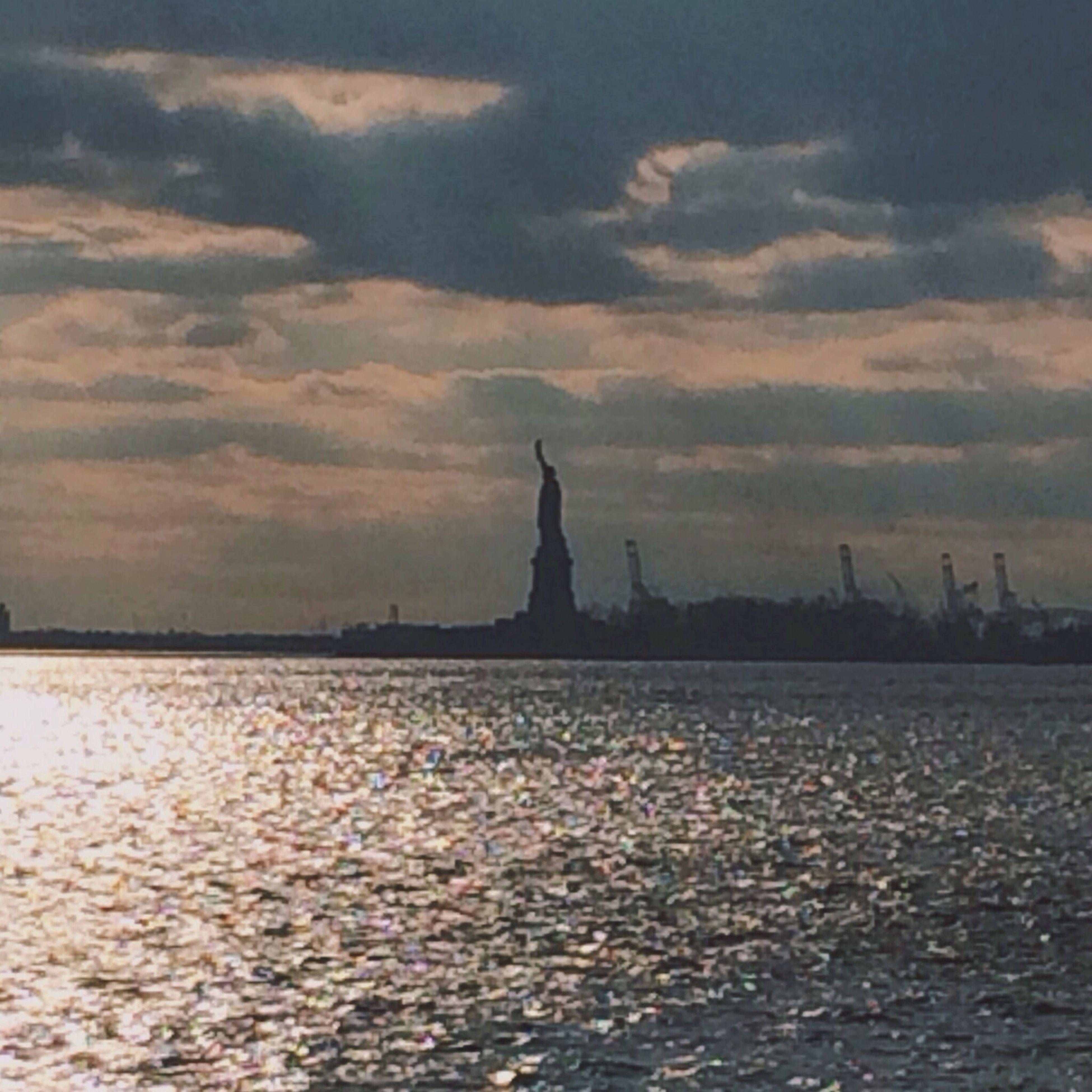 sky, water, sunset, architecture, built structure, building exterior, cloud - sky, silhouette, waterfront, statue, religion, cloudy, sculpture, human representation, dusk, spirituality, famous place, travel destinations, place of worship, sea