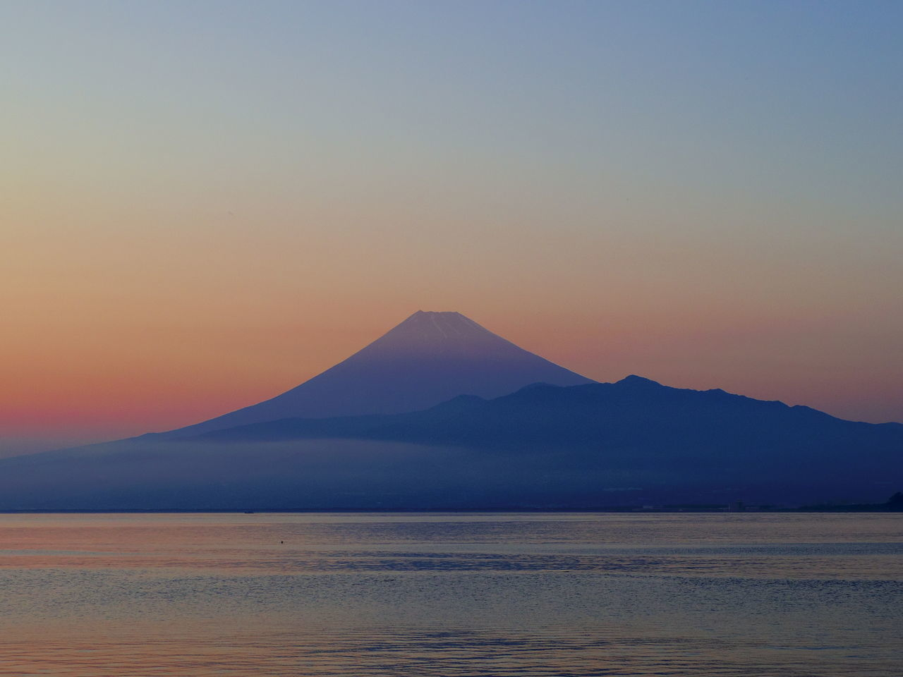Scenic View Of Sea By Silhouette Mountains Against Sky During Sunset