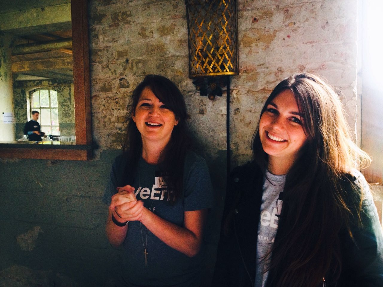 Portrait of friends smiling while standing against wall