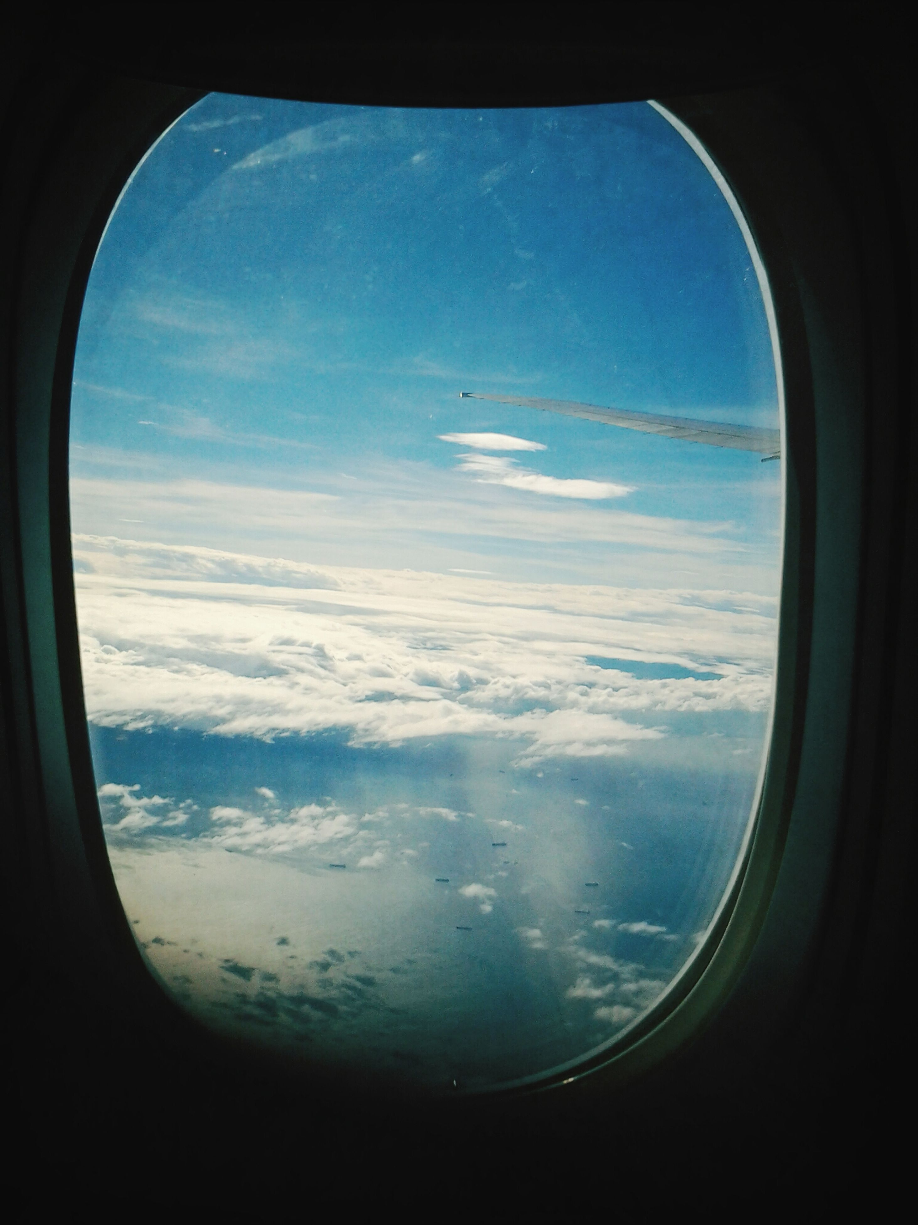 airplane, air vehicle, transportation, flying, mode of transport, window, vehicle interior, aircraft wing, aerial view, transparent, mid-air, sky, glass - material, travel, part of, blue, journey, scenics, beauty in nature, cropped