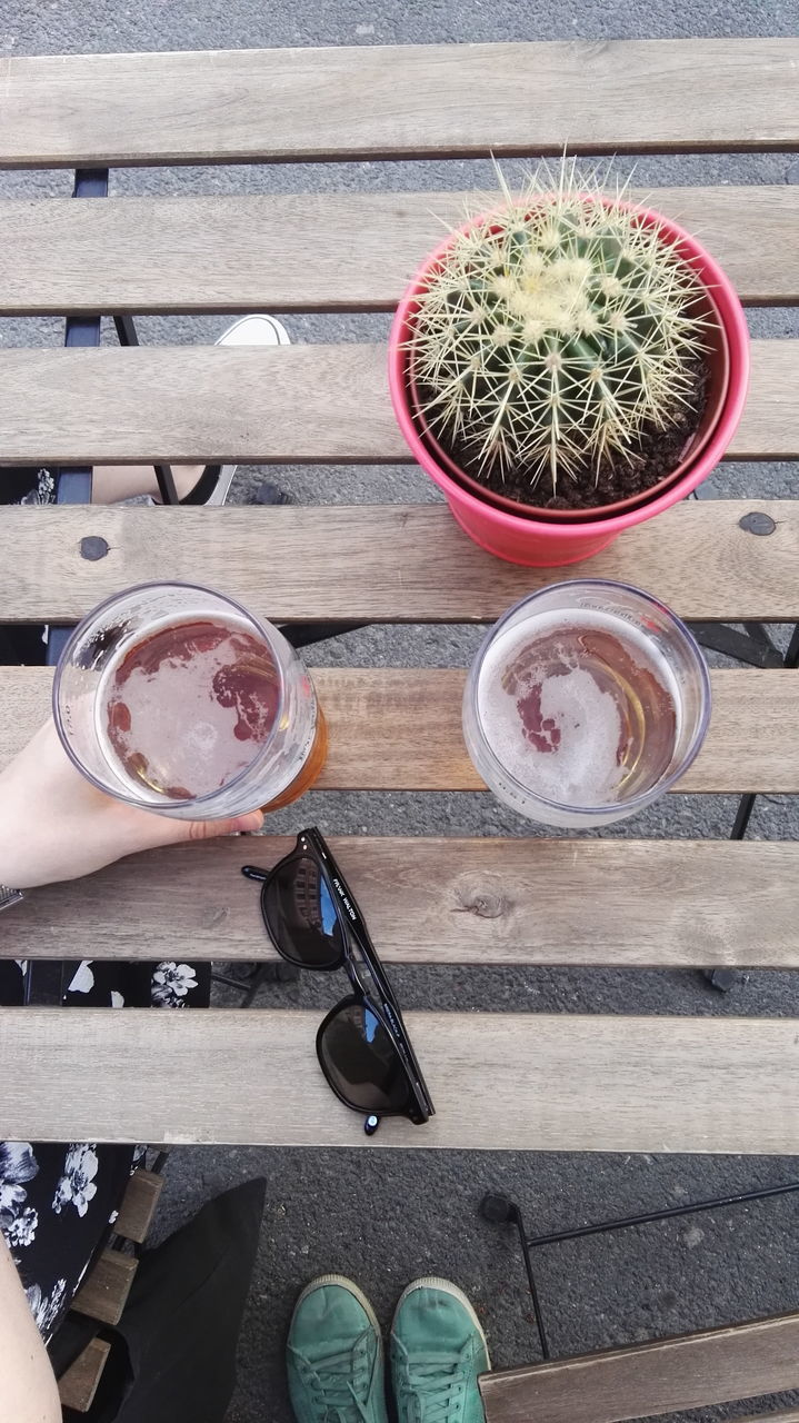drink, refreshment, high angle view, food and drink, drinking glass, table, wood - material, freshness, day, human body part, directly above, outdoors, plant, one person, lifestyles, healthy eating, real people, close-up, human hand, people