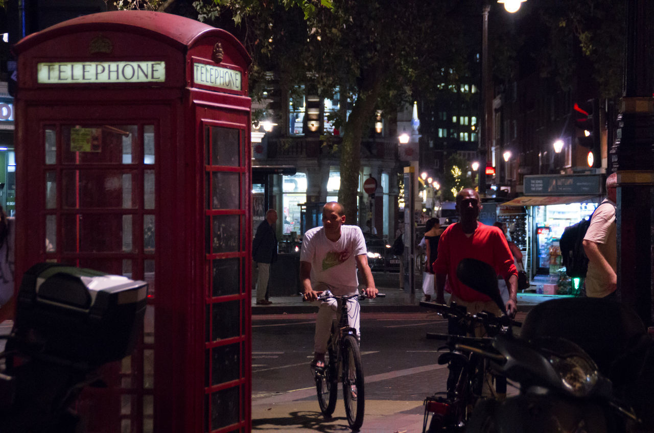 transportation, bicycle, mode of transport, land vehicle, city, real people, communication, city life, architecture, street, cycling, built structure, outdoors, riding, telephone booth, building exterior, helmet, red, day, tree, pay phone, one person, people