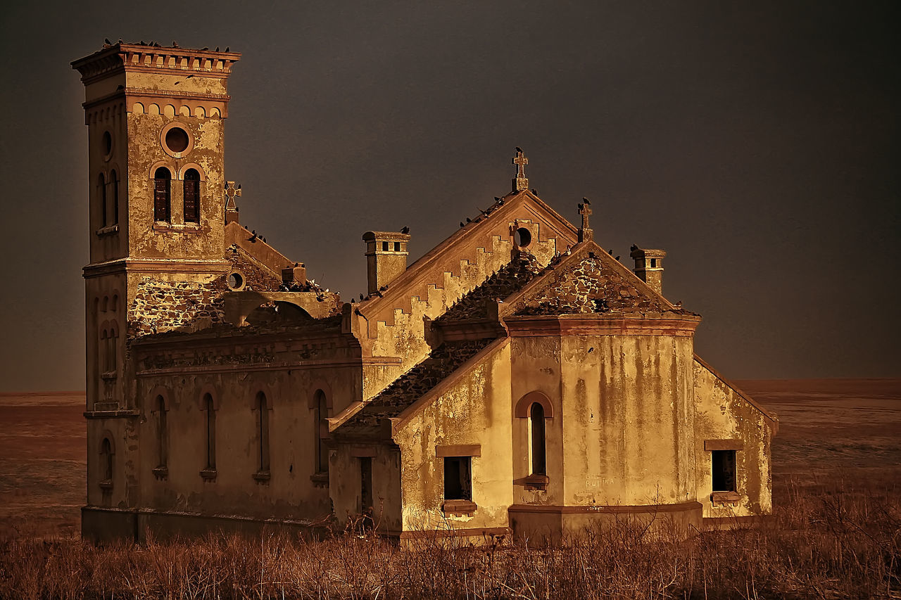 """A Lost And Forgotten Gothic Monastery Culelia, Colilia or Colelia was a village in Dobrogea, now gone, which was located between Cogealac and Gradina. It was founded in 1880 and inhabited until 1940 by Germans, when was carrying the German name of Colelie, Kolelie or Kulelie . Once the Germans were displaced in the Third Reich in 1940, the village remained very sparsely populated. In 1945 Colelia was repopulated with Romanians and Macedonians, who were given land and the existing homes. Roman-Catholic Church, which was built by the Germans in 1934 , returned to the Romanian Orthodox Church. Since there was no dispensary in the village or school, people were forced to leave the town, so in 1966 it remained empty. In 2006, in addition to the church which was left standing, the Holy Monastery of nuns was founded """"Entrance of the Mother of God in the Church"""". Besides the function of monastery, the settlement has as a mission a charitable activity and social, which is to house and support the elderly deprived of opportunities,with no pension and with very small income. Architecture Building Exterior Cathedral Church Colilia Cross Deserted Town Forgotten Gothic Gothic Architecture Gothic Church History Monastery Old Old Buildings Place Of Worship Postprocessing Religion Romania Ruined Ruined Building Ruined Monastery Ruines Spirituality Vignette"""