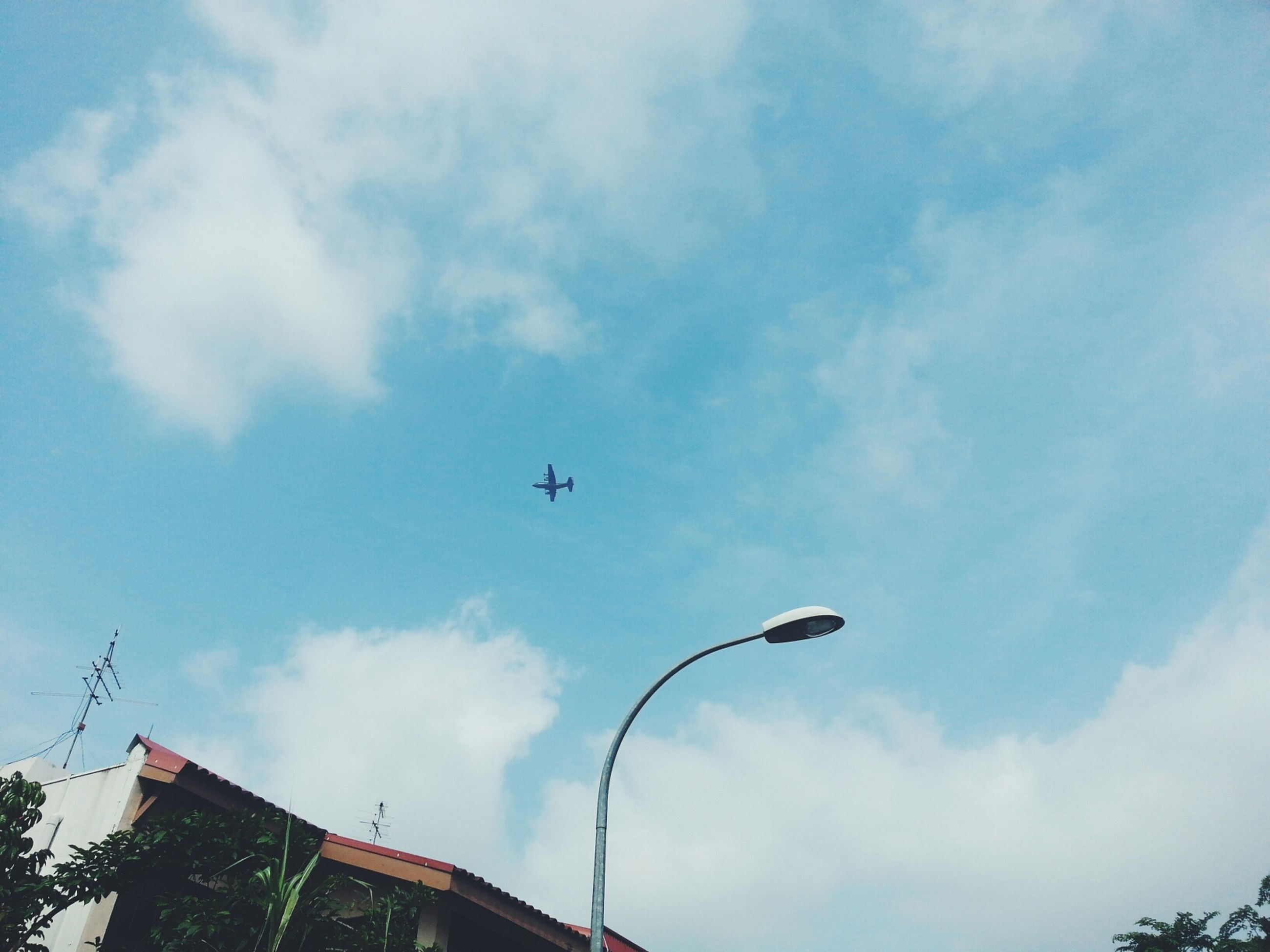 low angle view, sky, built structure, architecture, building exterior, cloud - sky, transportation, street light, cloud, mode of transport, cloudy, day, outdoors, flying, air vehicle, lighting equipment, high section, airplane, no people, blue