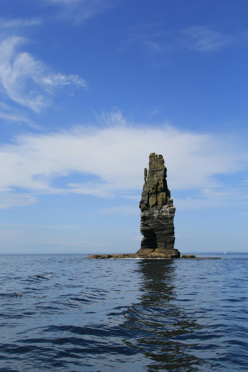 Rock Formation Amidst Sea Against Sky