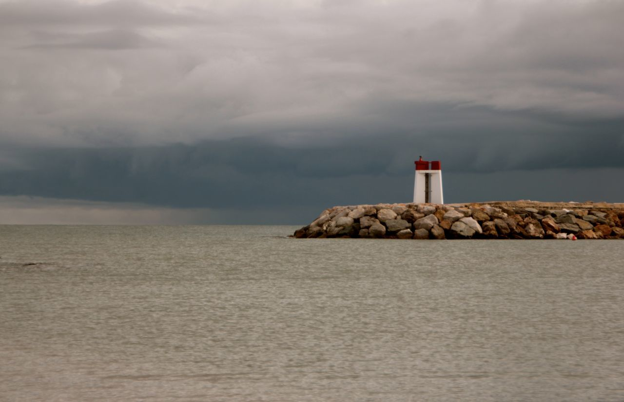Lighthouse By River Against Cloudy Sky