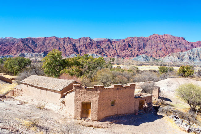 Rustic old building made of adobe with dramatic red hills rising in the background in the small town of Chacopampa near Tupiza, Bolivia Amazing Andes Beauty Bolivia Cactus Canyon Color Countryside Desert Destination Formation Formations High Hills House Landscape Mountain Nature Rock Rocks Rural South America Travel TUPIZA Valley