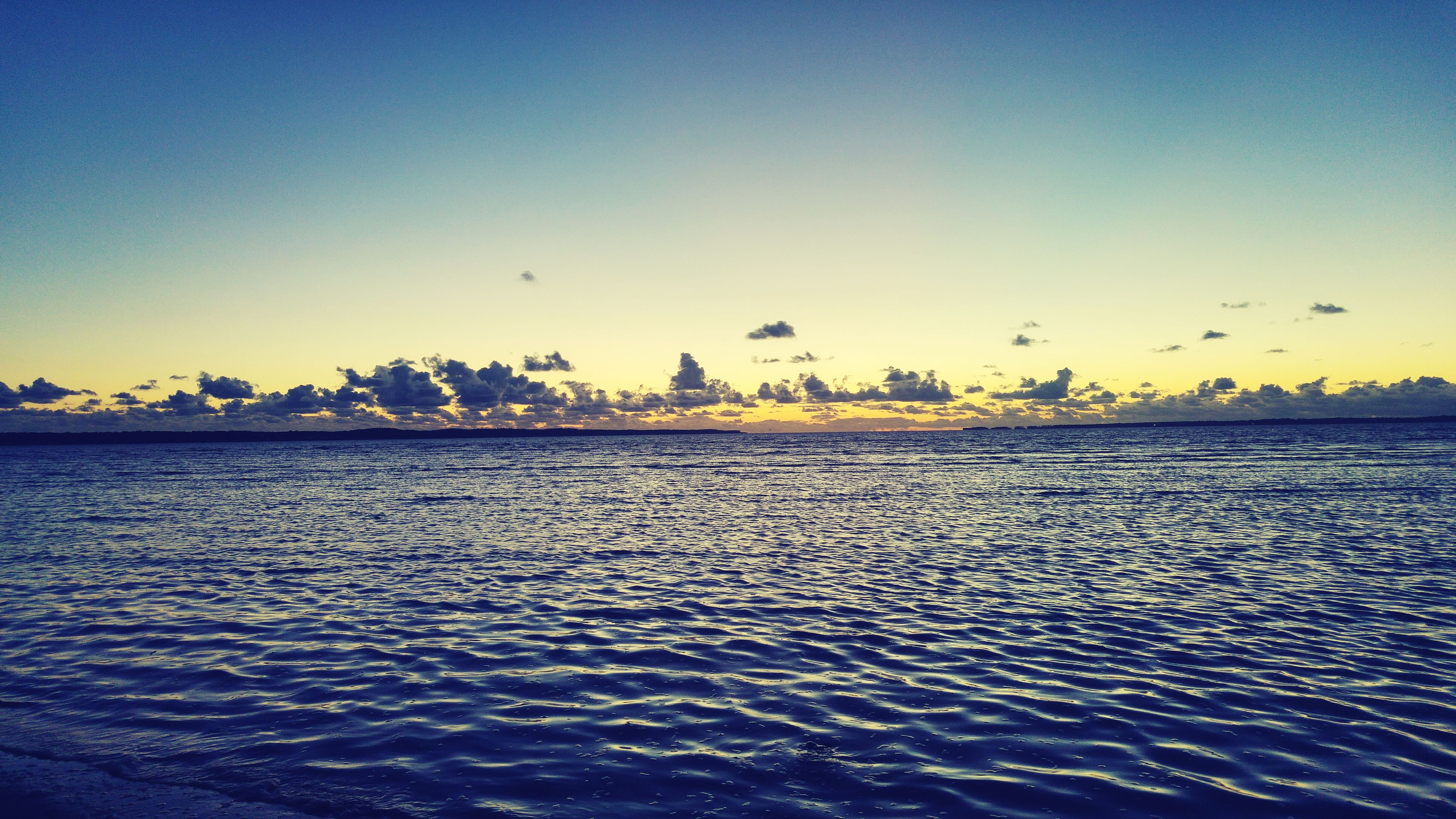 water, beach, sea, clear sky, sky, sand, beauty in nature, outdoors, no people, nature, sunset, architecture, building exterior, day, built structure, city, tranquility, scenics, cityscape