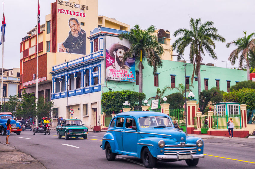 Santiago de Cuba is often referred to as birthplace of the Cuban revolucion. Posters of Fidel Castro advertise the revolution - Santiago de Cuba, CUBA in January 2015 Architecture Blue Taxi Car City Communism Communist Cuba Cuba Collection Day Fidel Castro Oldtimer Outdoors Palm Tree People Propaganda Revolution Santiago Santiago De Cuba Sky Socialism Taxi Tree
