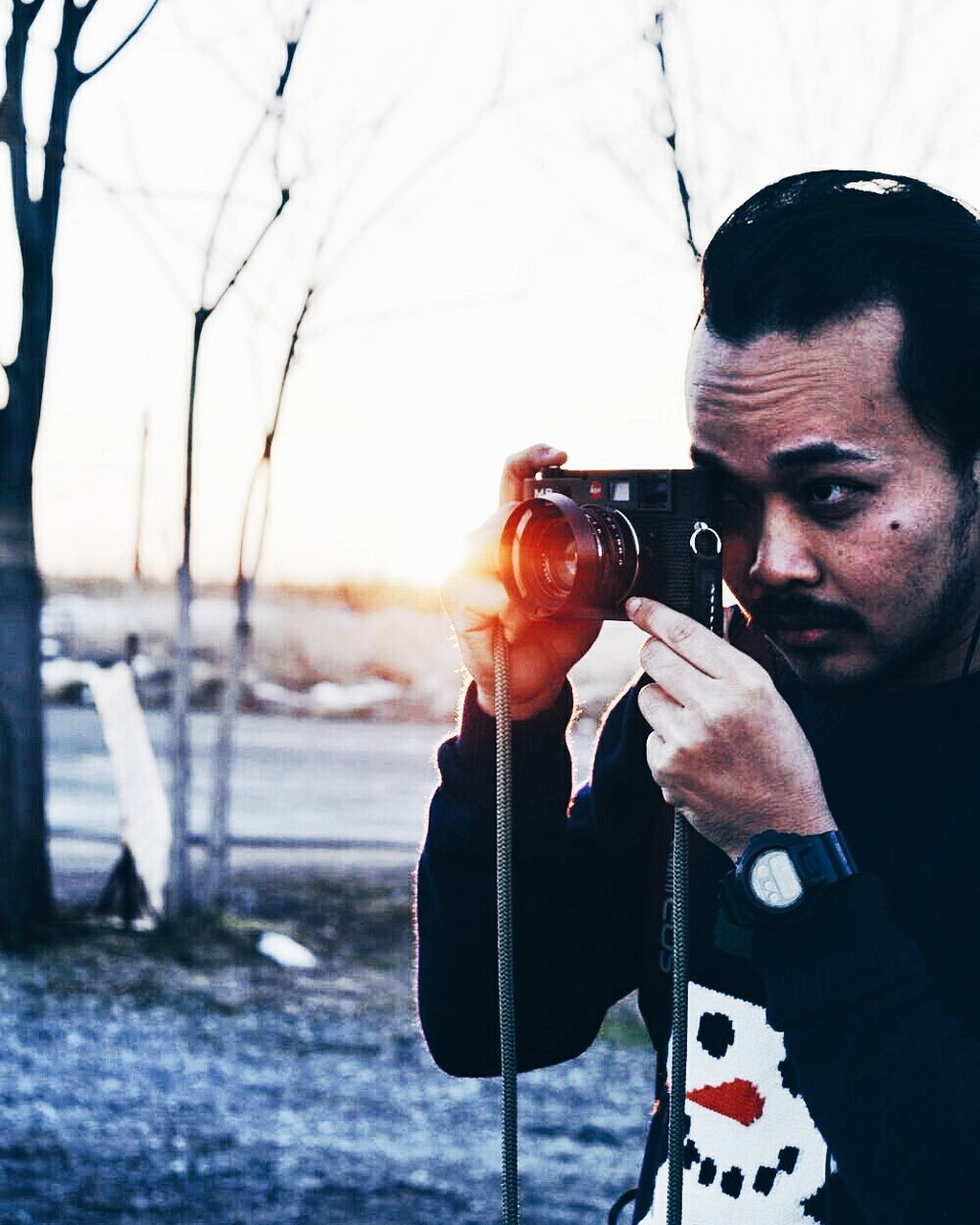 real people, one person, photographing, photography themes, leisure activity, photographer, camera - photographic equipment, holding, digital camera, lifestyles, outdoors, technology, camera, men, day, slr camera, young adult, digital single-lens reflex camera, nature, sky, close-up, people