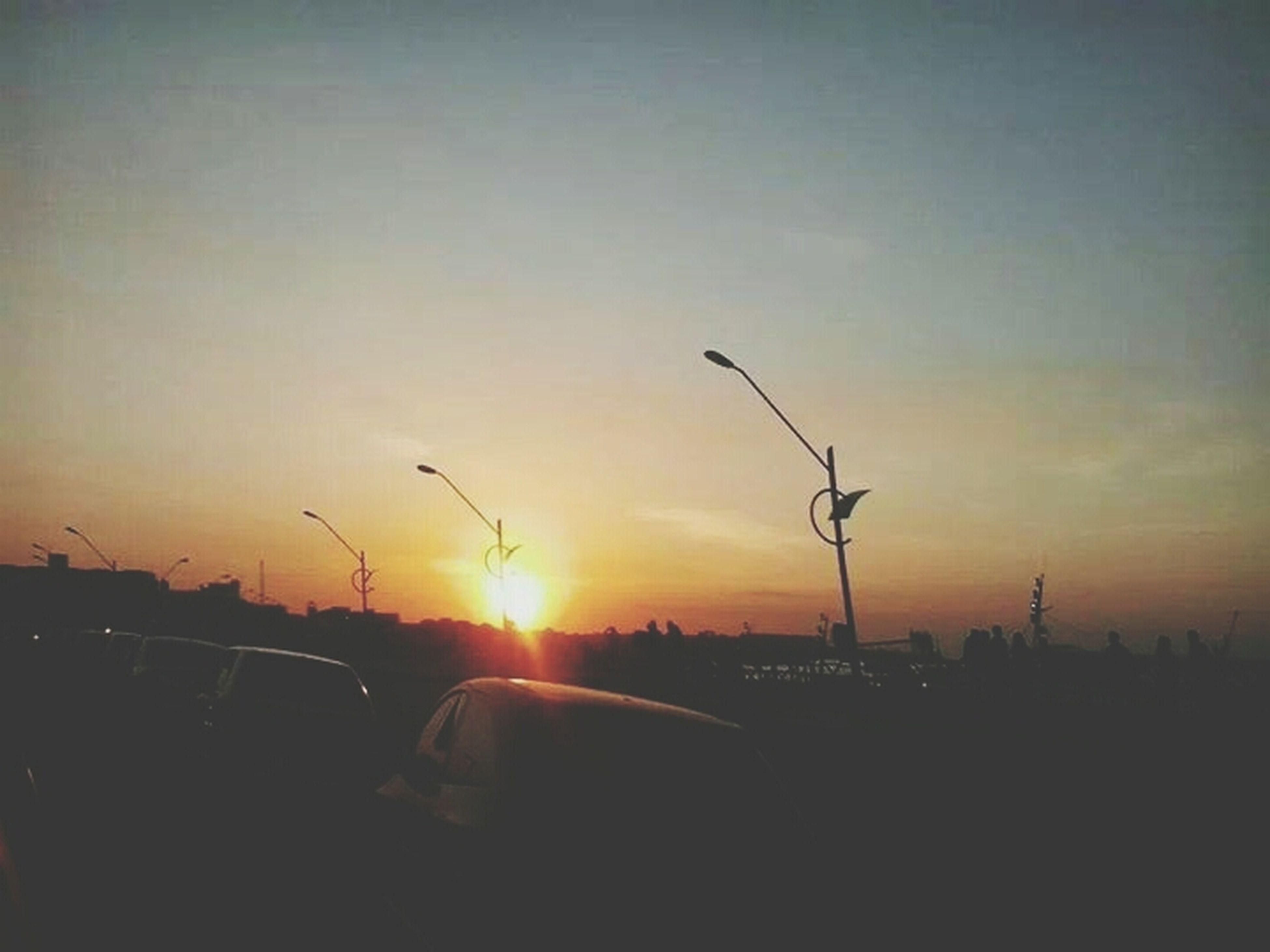 sunset, sun, silhouette, orange color, transportation, sky, car, sunlight, mode of transport, nature, sunbeam, beauty in nature, land vehicle, scenics, bird, flying, lens flare, outdoors, street light, tranquil scene