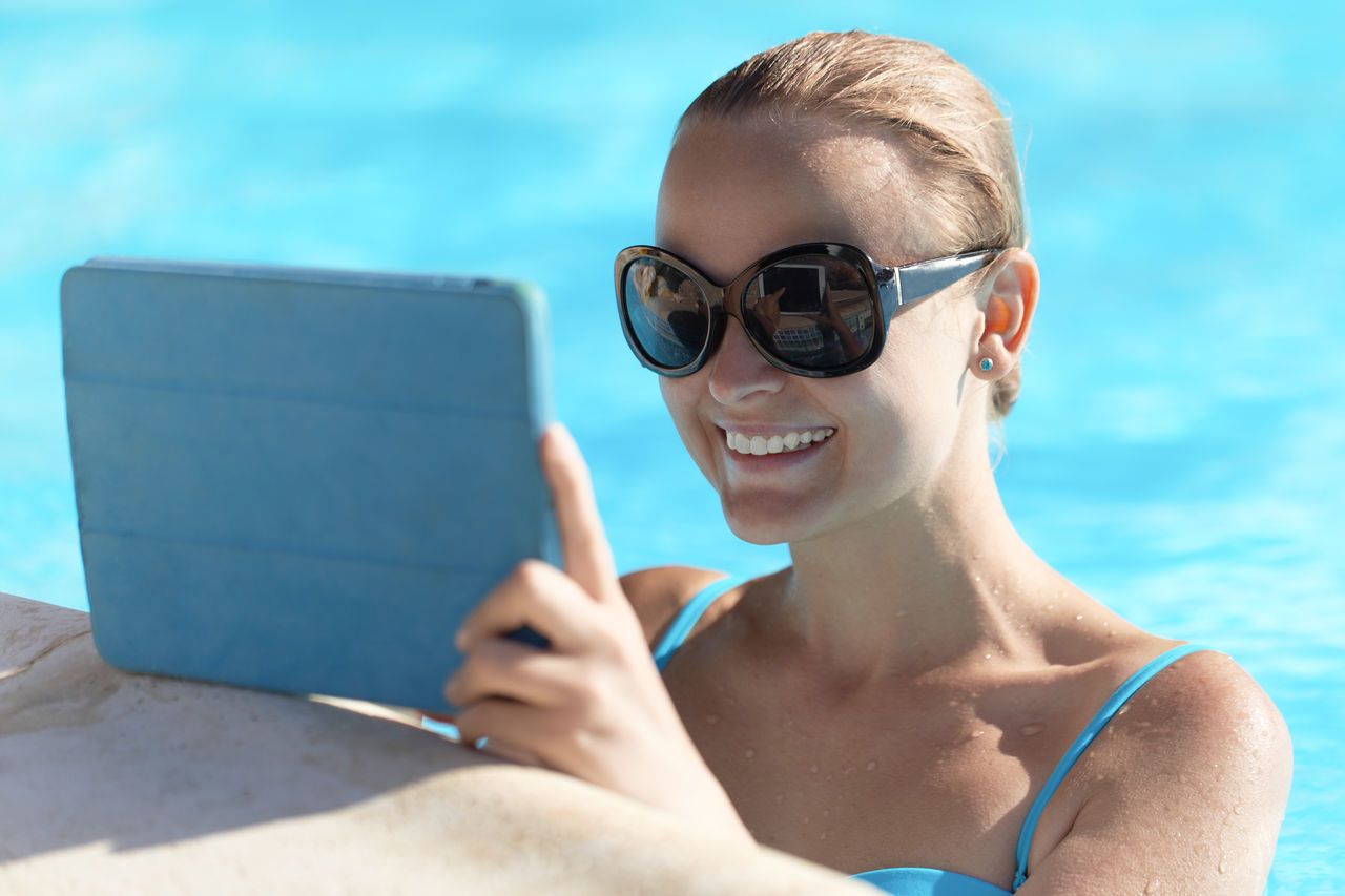 Happy Woman Holding Digital Tablet In Swimming Pool