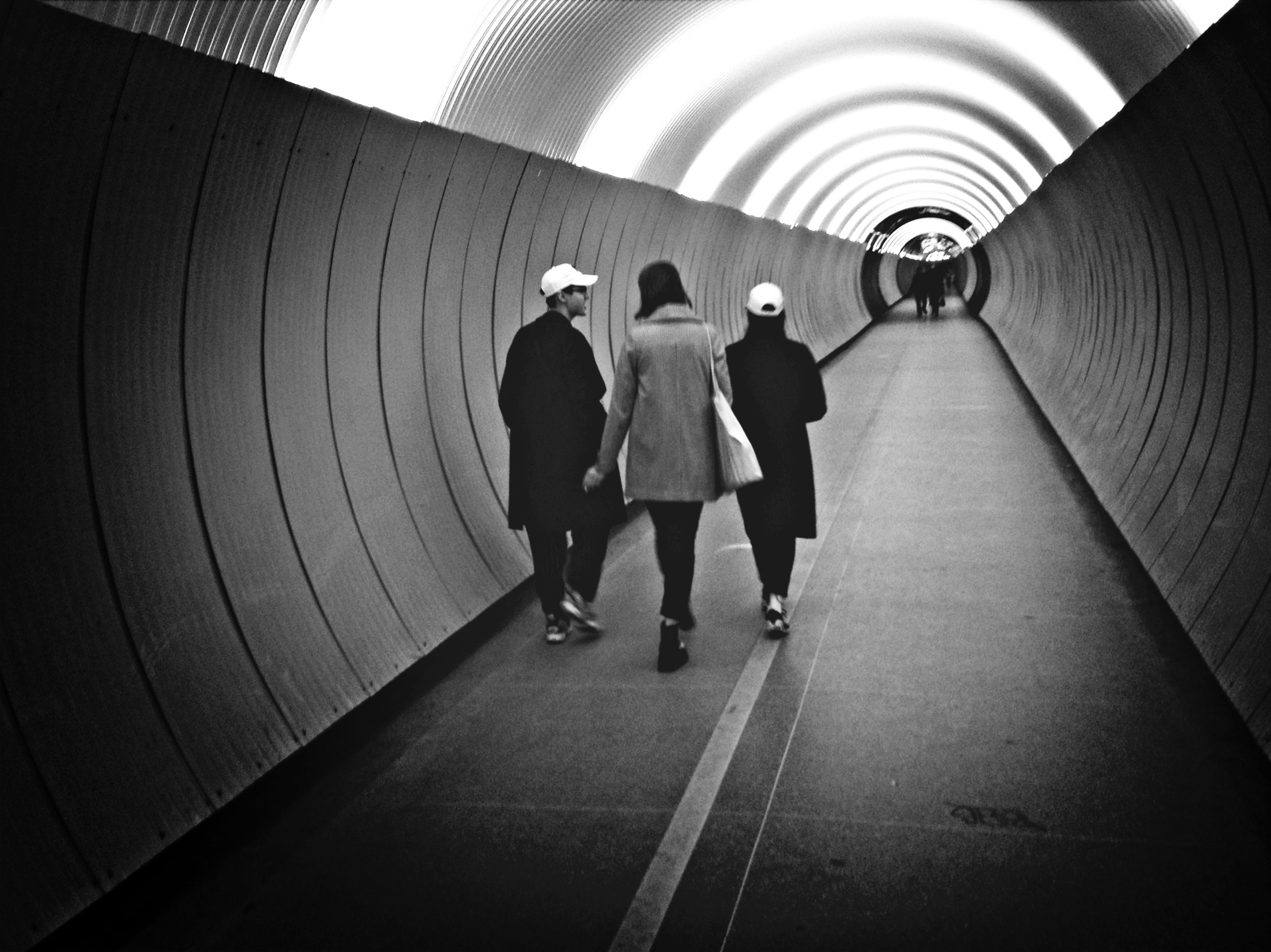walking, full length, rear view, indoors, the way forward, men, lifestyles, tunnel, person, leisure activity, togetherness, diminishing perspective, transportation, vanishing point, on the move, architecture, built structure