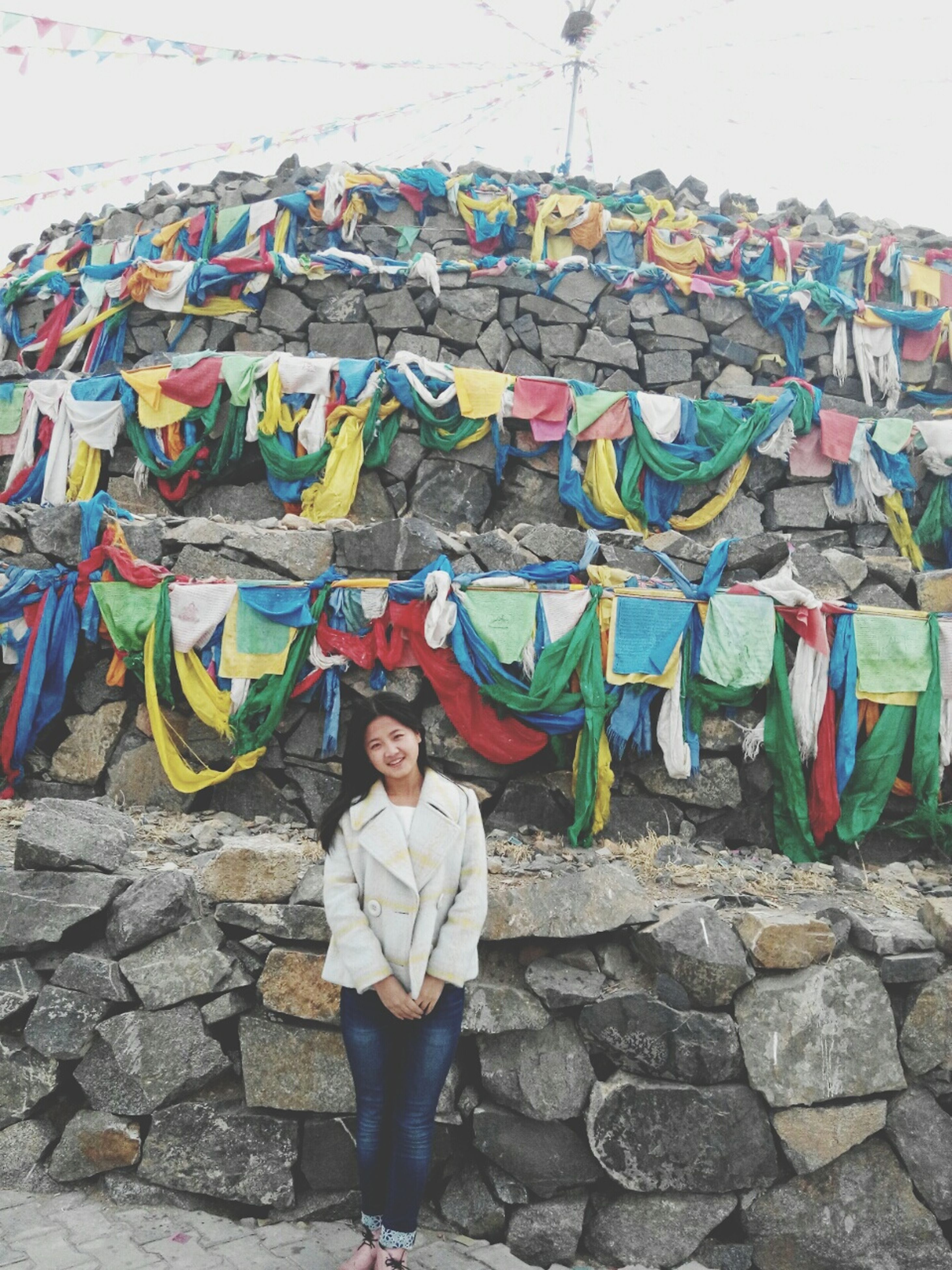 lifestyles, casual clothing, leisure activity, full length, standing, multi colored, traditional clothing, person, graffiti, built structure, looking at camera, wall - building feature, day, young adult, front view, men, outdoors
