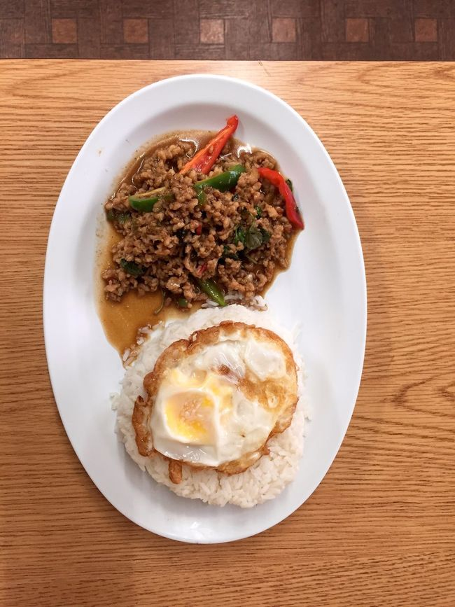 Chicken Pad Kra Pow with steamed rice and fried egg. Thai Food Ready-to-eat Freshness Plate White Rice Fried Egg Ground Chicken Spicy Meal Indulgence Lunch Dinner Chili  Close-up Elevated View Selective Focus