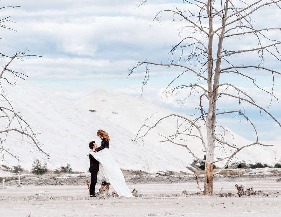 The bride with red hair stands on the dried-up stump and hugs the groom on the background of the desert with withered trees, mountains of sand. Modern wedding dress and suit. Adults Only Beauty In Nature Cloud - Sky Communication Couple - Relationship Desert Desert Landscape Embracing Love Outdoors Romance Sand Dune Togetherness Tree Trees Two People Wedding Wedding Photography Weddings Around The World Welcome To Black Withered  The Secret Spaces