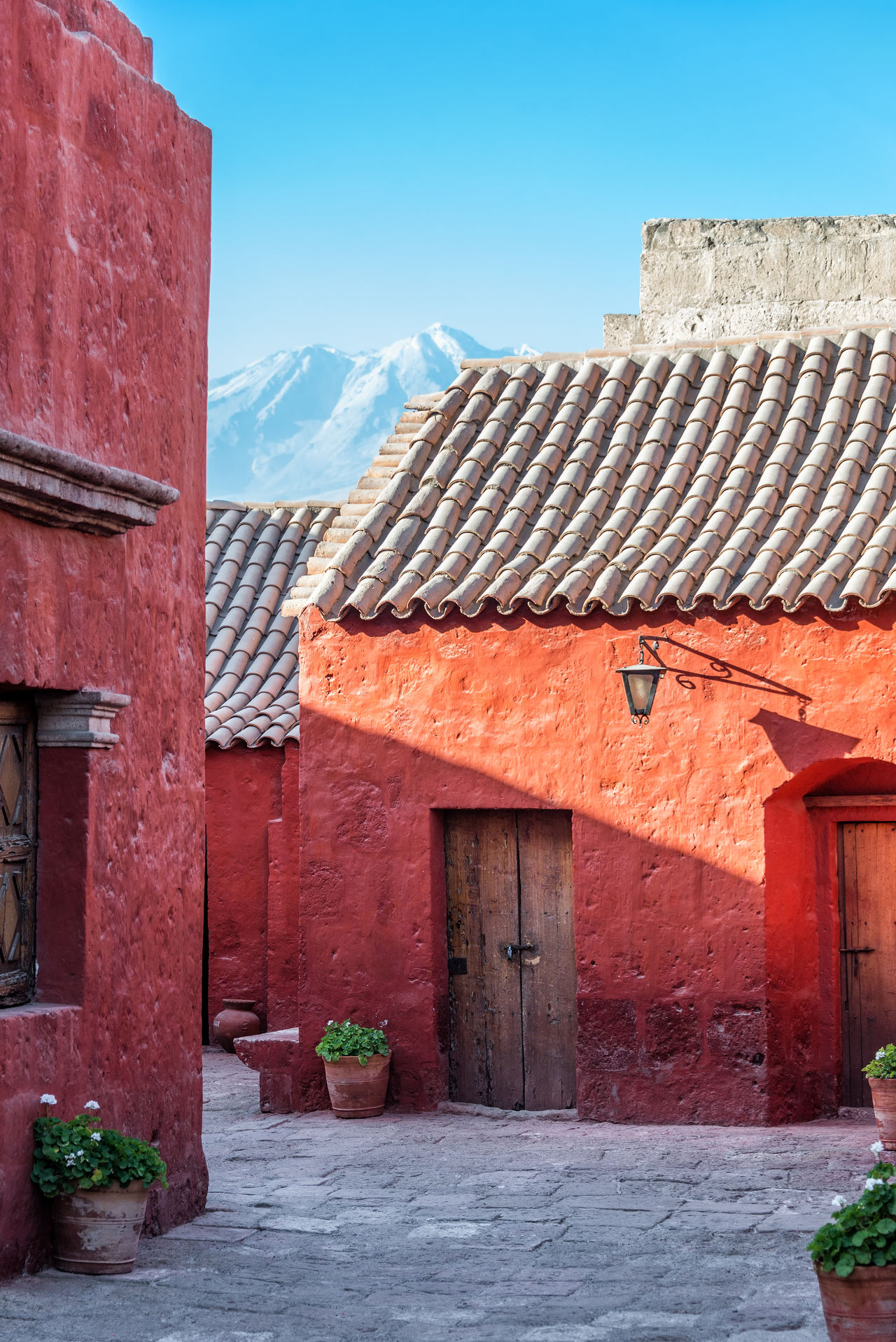 Beautiful red colonial architecture of Santa Catalina Monastery with Chachani volcano in the background Architecture Arequipa Catholic Catholicism Chachani Chachani Volcano Colonial Colonial Architecture Convent Door Doors Flower Flowers Historic Interior Monastery Mountain Peru Relaxing Religion Santa Catalina Santa Catalina Monastery Volcano