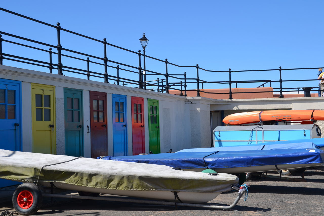 Architecture Blue Canoes Clear Sky Day Development Man Made Object No People Railing Seaside Town Transportation