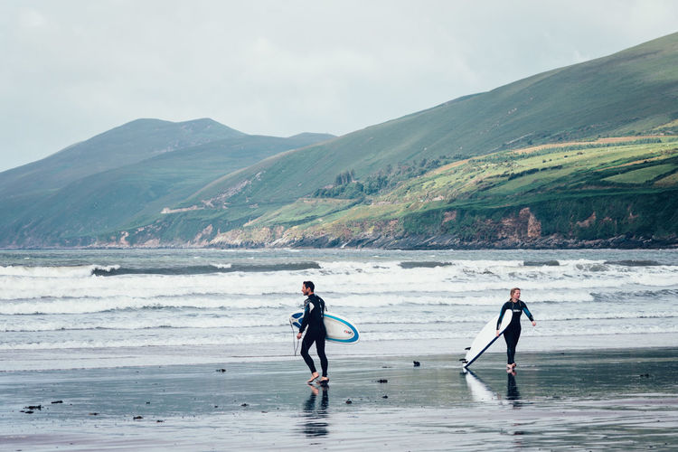 Beauty In Nature Exercising Ireland Mountain Ocean Outdoors People Sea Sky Sky And Clouds Sport Sports Clothing Surf Surf Bay Surfers Togetherness Two People Vacations
